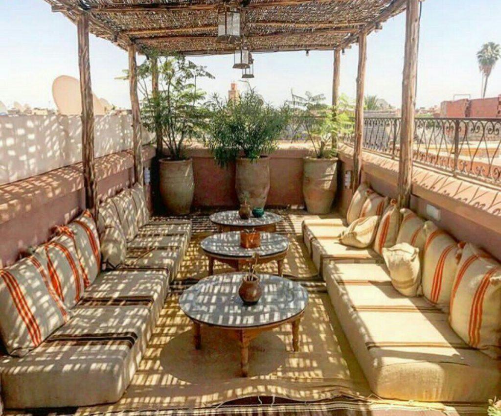 rooftop di un riad marocchino con cuscini a terra e piante grasse