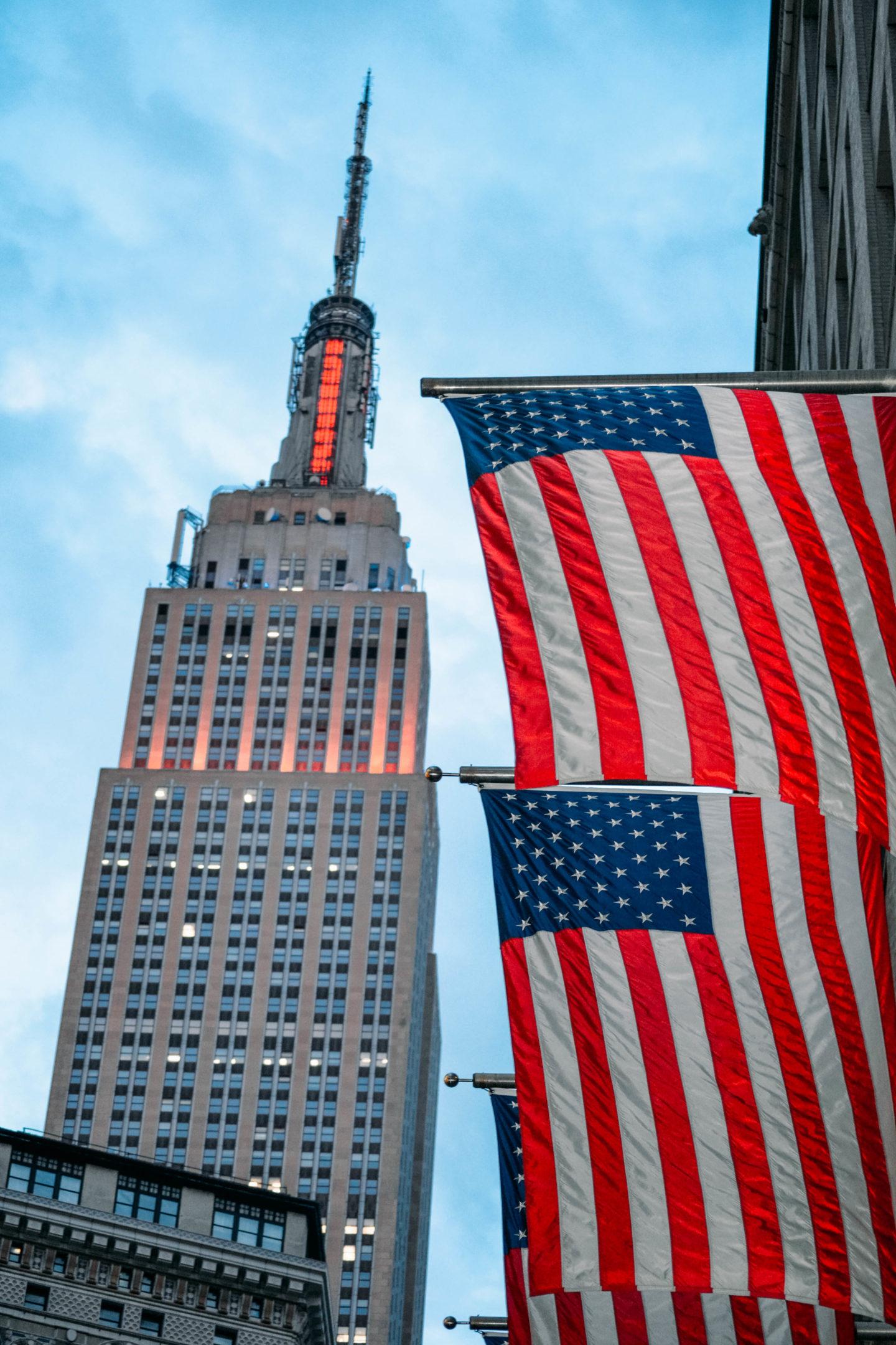 punta dell'empire state building e due bandiere americane
