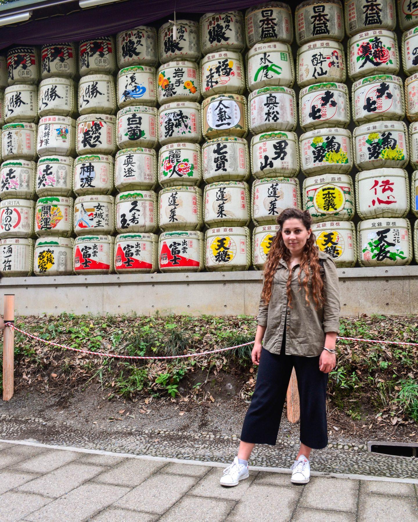 ragazza davanti parete di barili di sakè