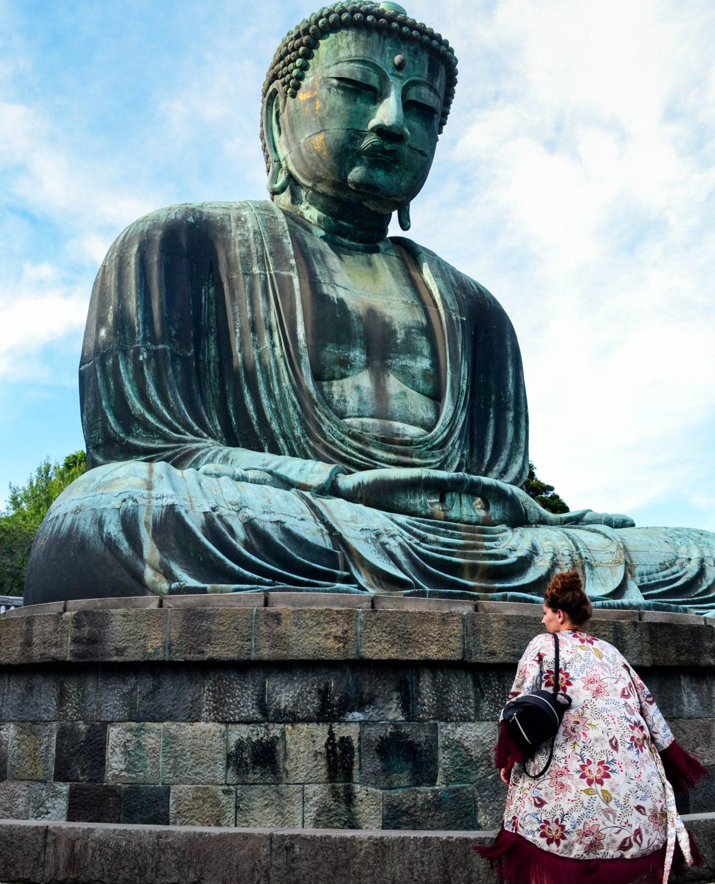 ragazza di spalle davanti a grande buddha seduto