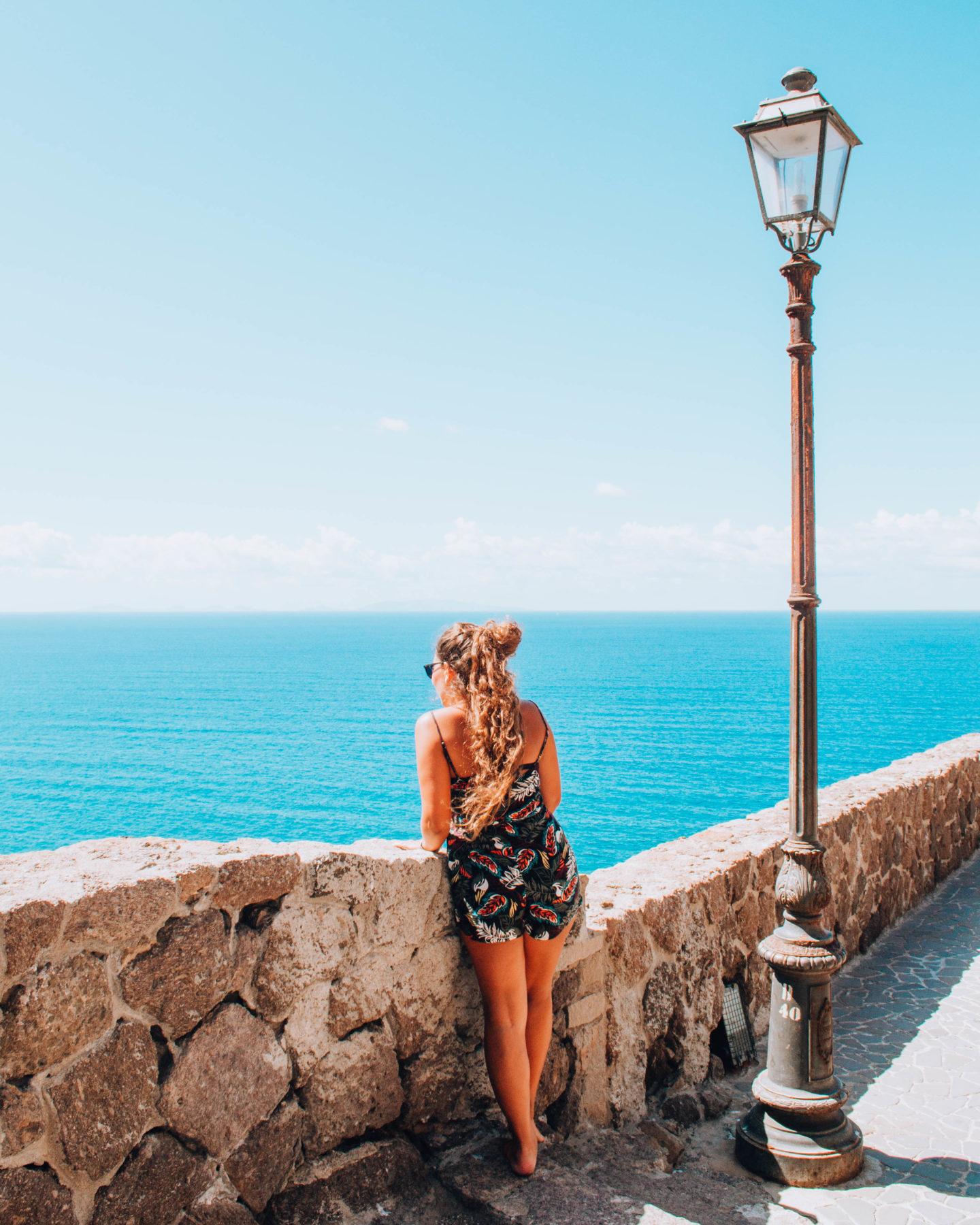 ragazza che si affaccia ad una terrazza sul mare sotto un lampione
