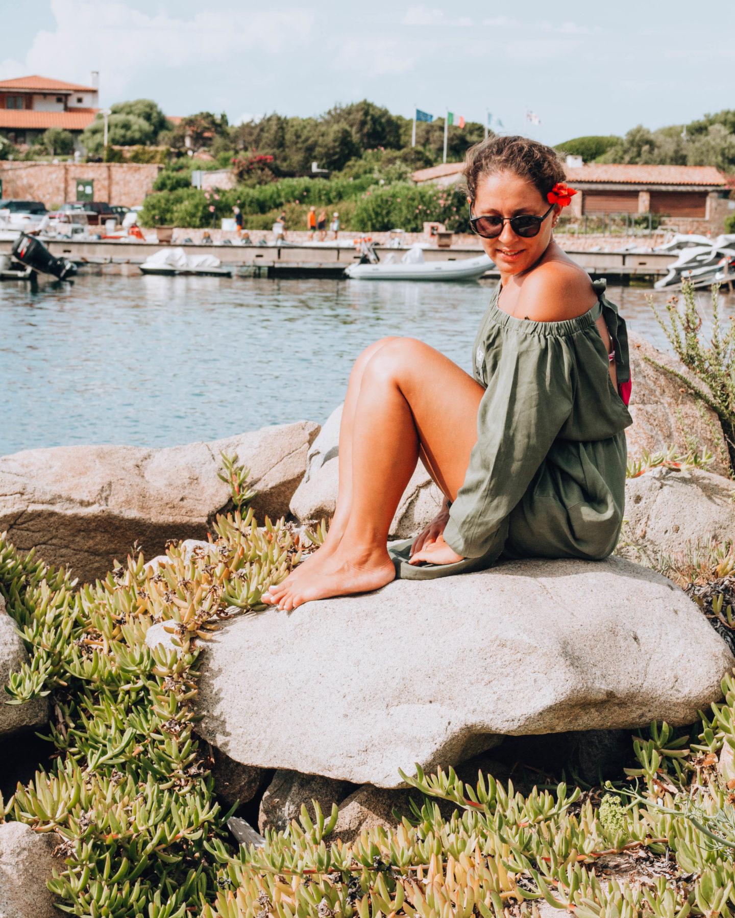 ragazza con fiore tra i capelli seduta su una roccia in una marina