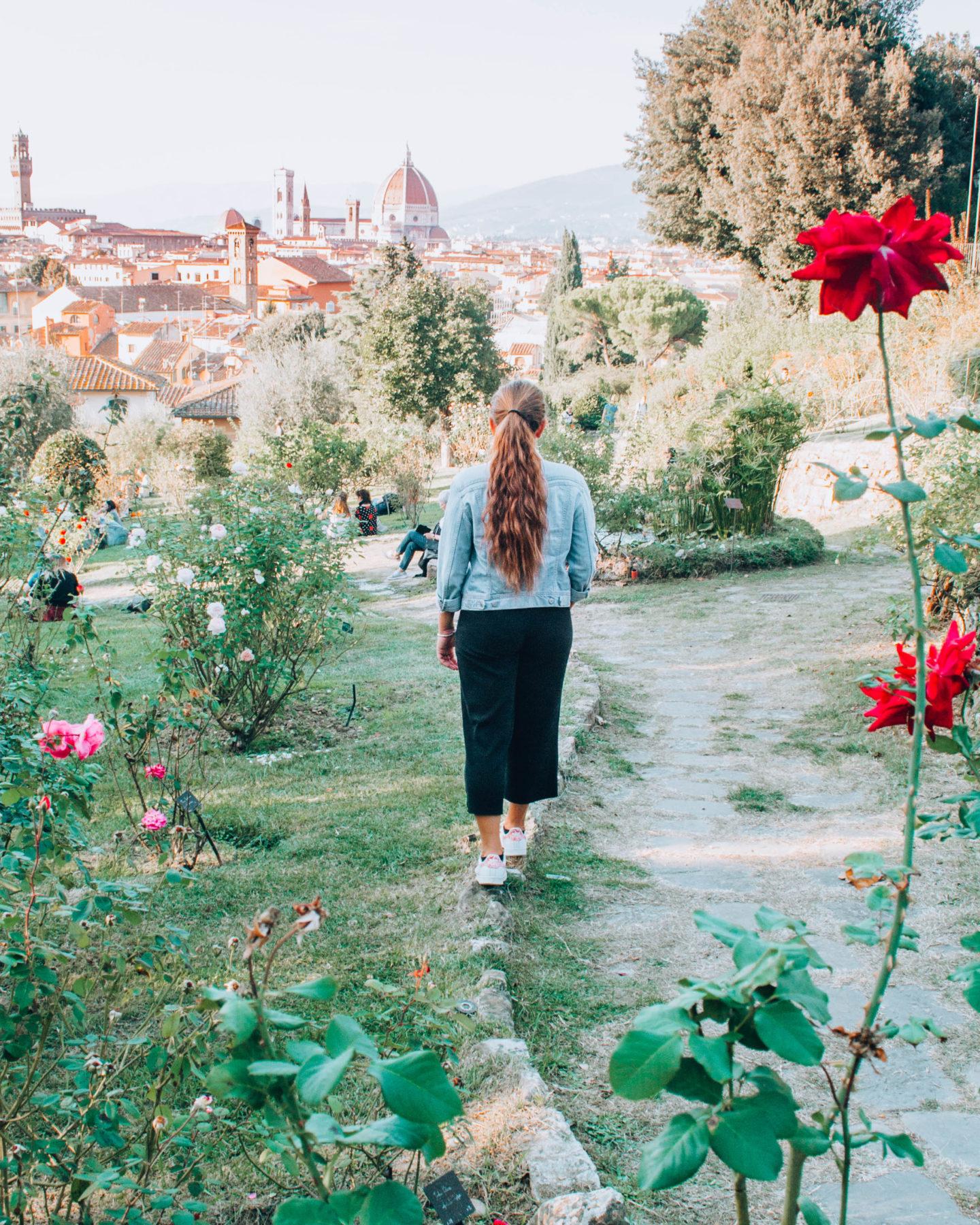 ragazza di spalle in un giardino di rose