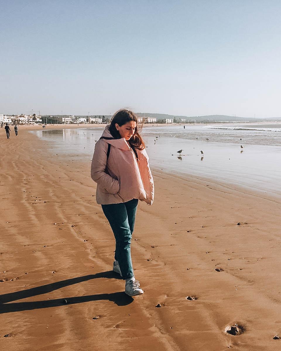ragazza che cammina su spiaggia d'inverno