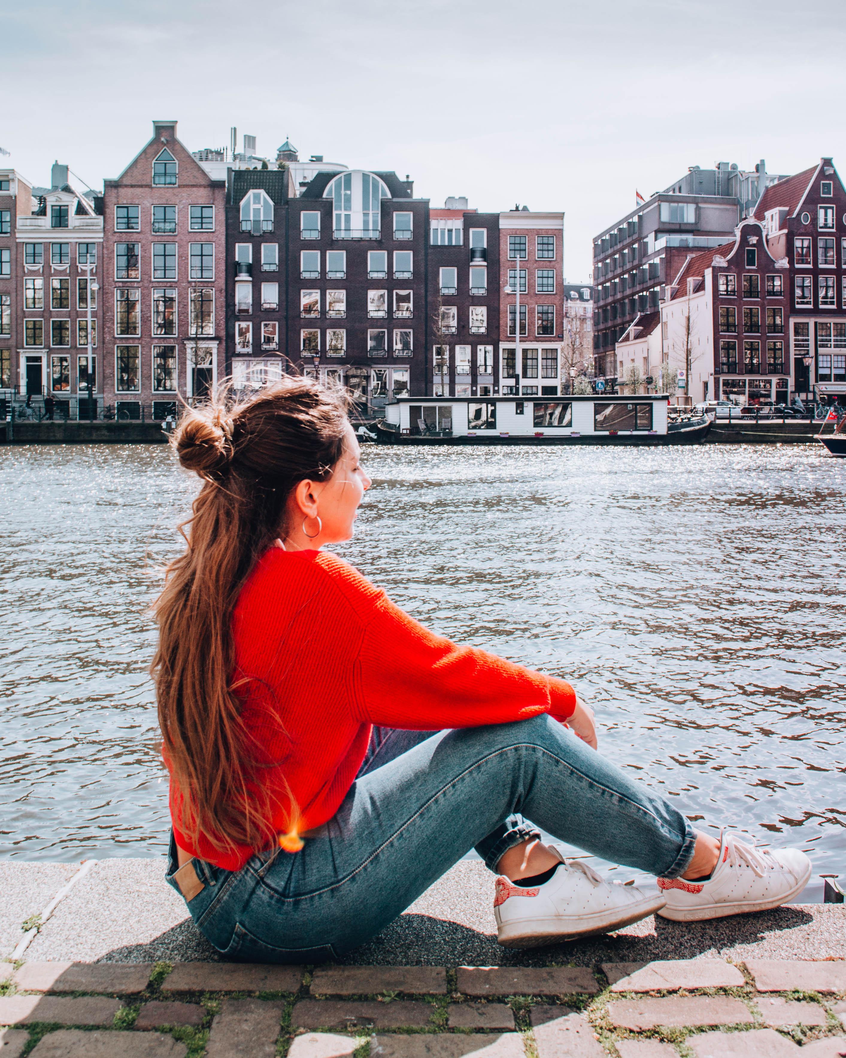 ragazza seduta sulla bachina di un canale