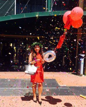 neolaureata in abito rosso che festeggia con coriandoli e palloncini rossi