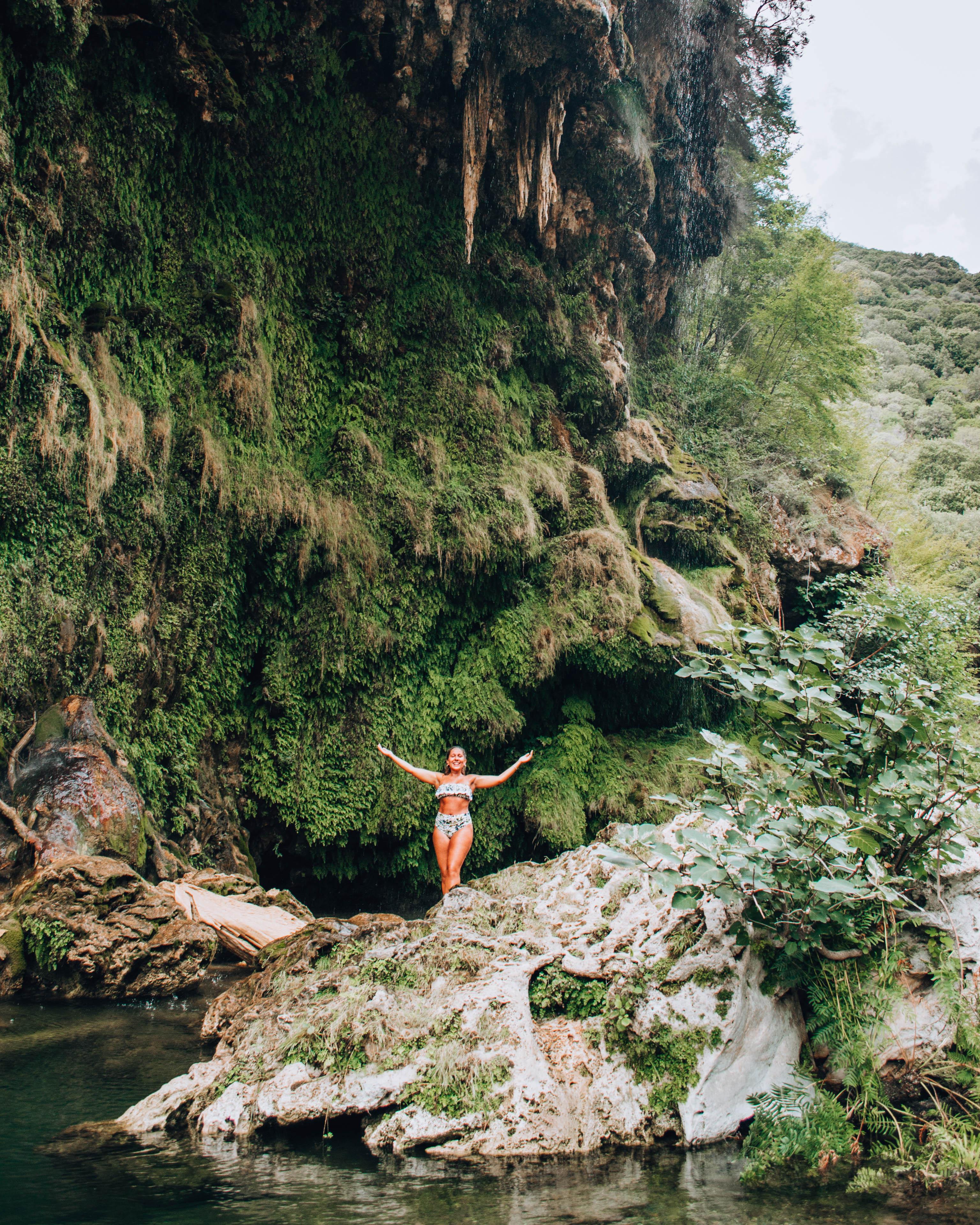 ragazza che fa bagno sotto cascata