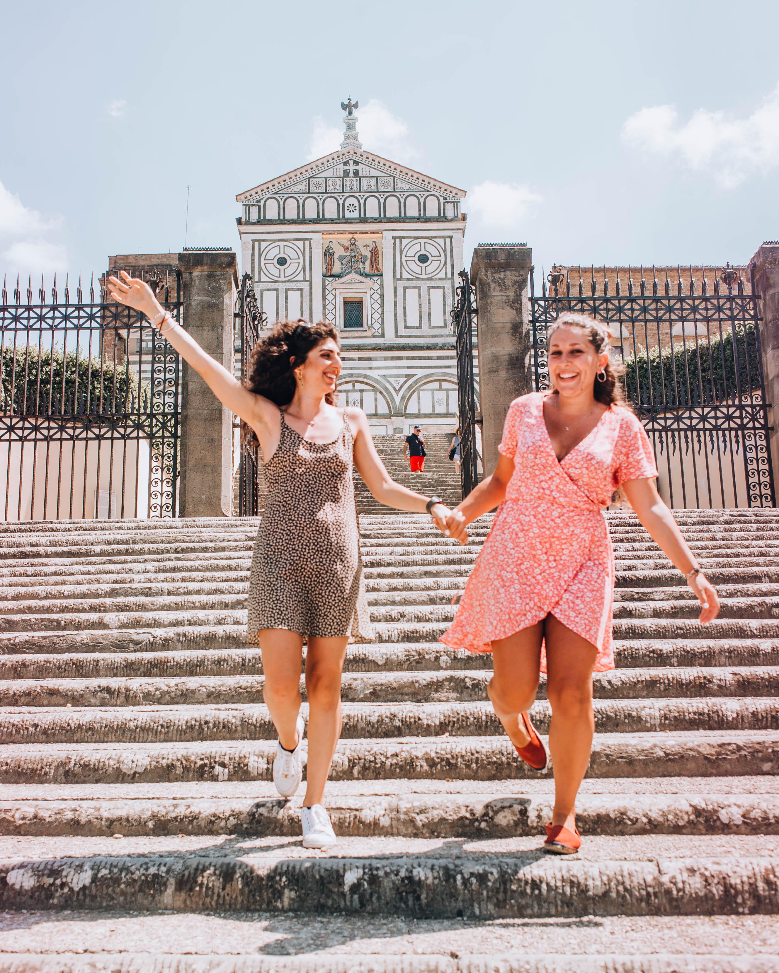 due ragazze con vestito su gradinata davanti a una chiesa