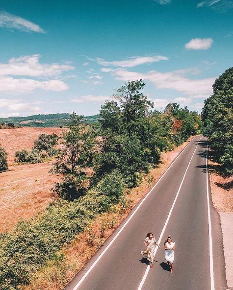 ripresa aerea di due ragazze che corrono su una strada di campagna