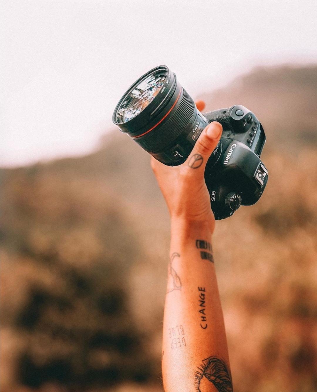 avambraccio tatuato che tiene in mano una macchina fotografica reflex