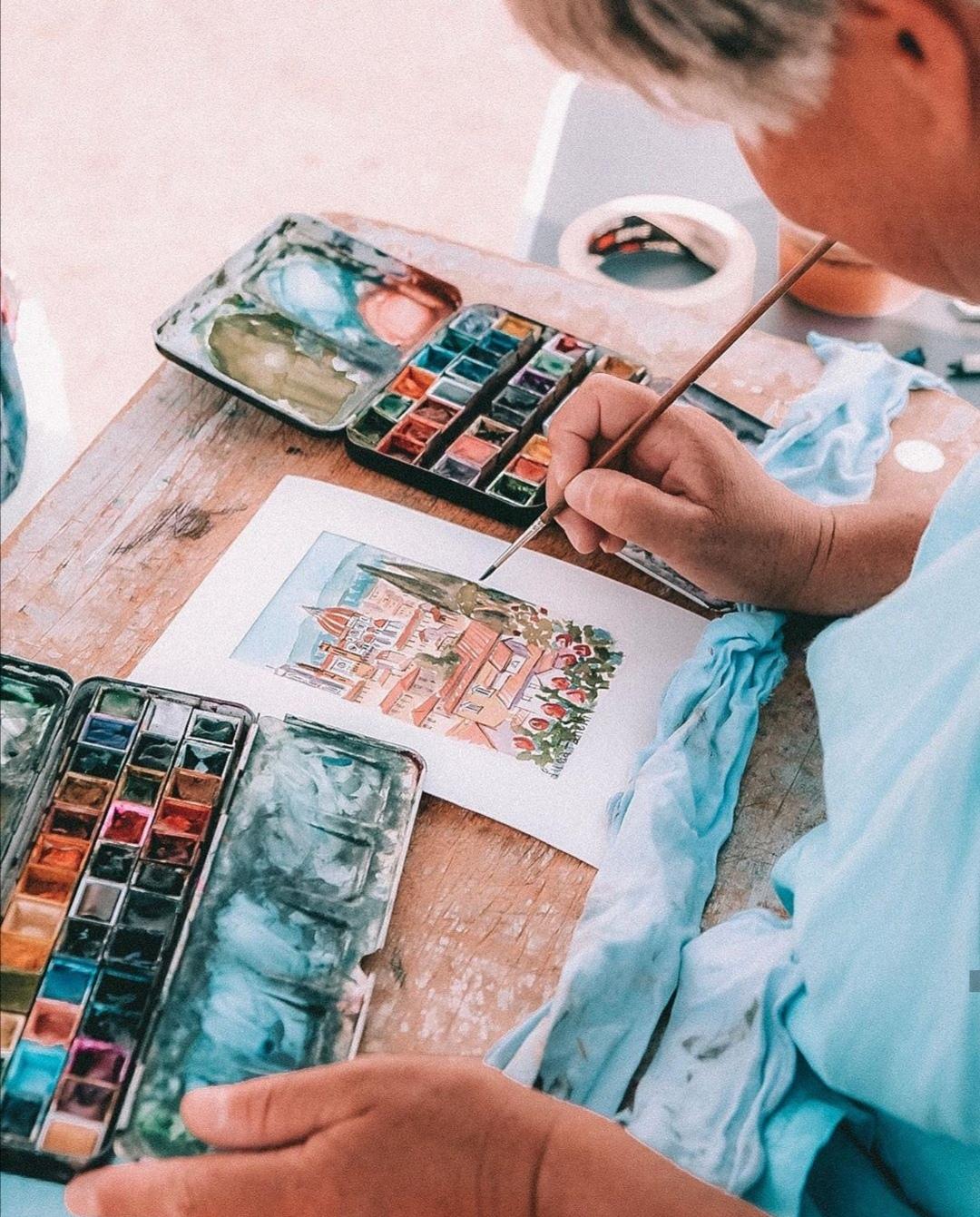 profilo di donna che dipinge con acquerelli, pennello e tavolozza