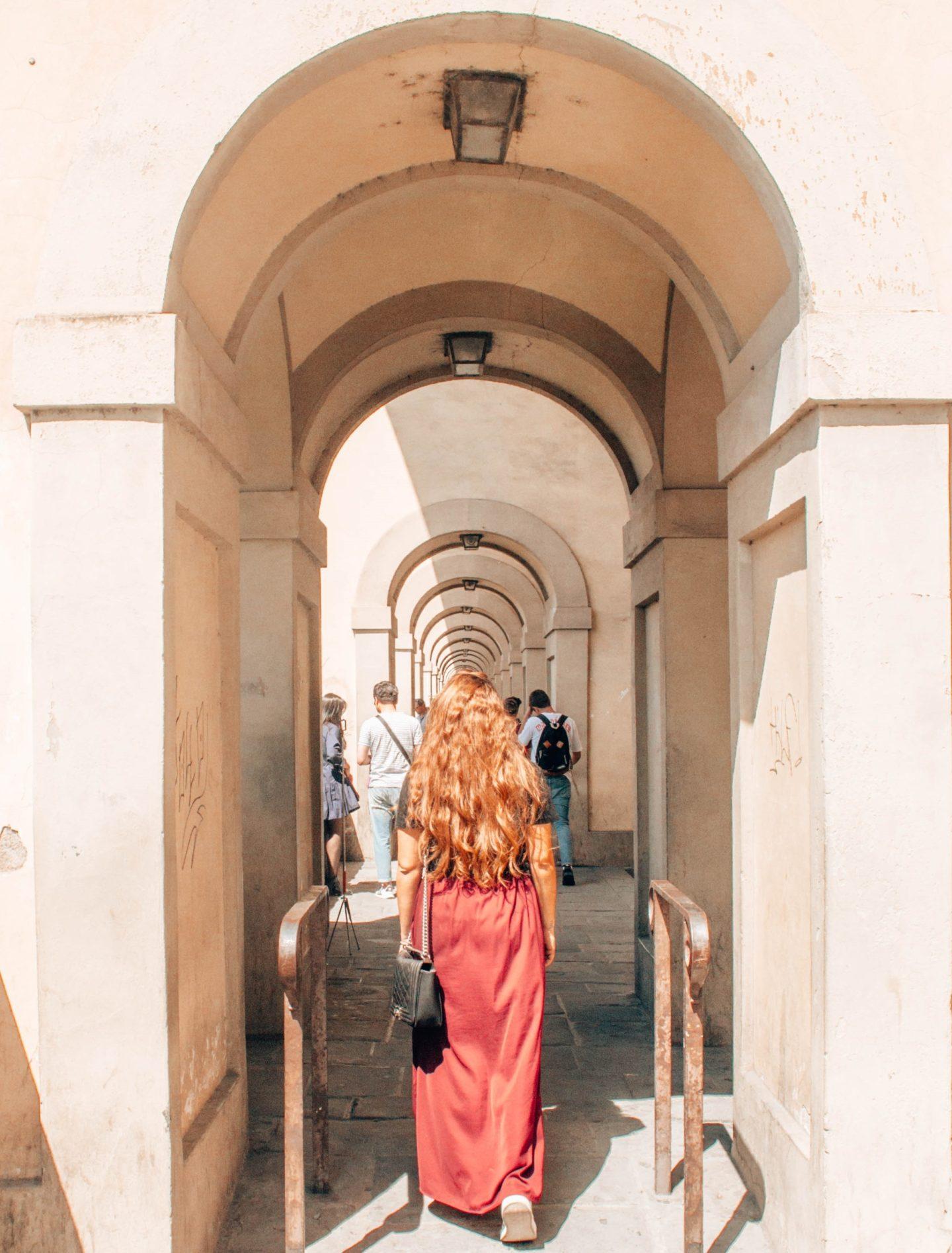 ragazza di spalle con gonna lunga e rossa sotto un arco prospettico
