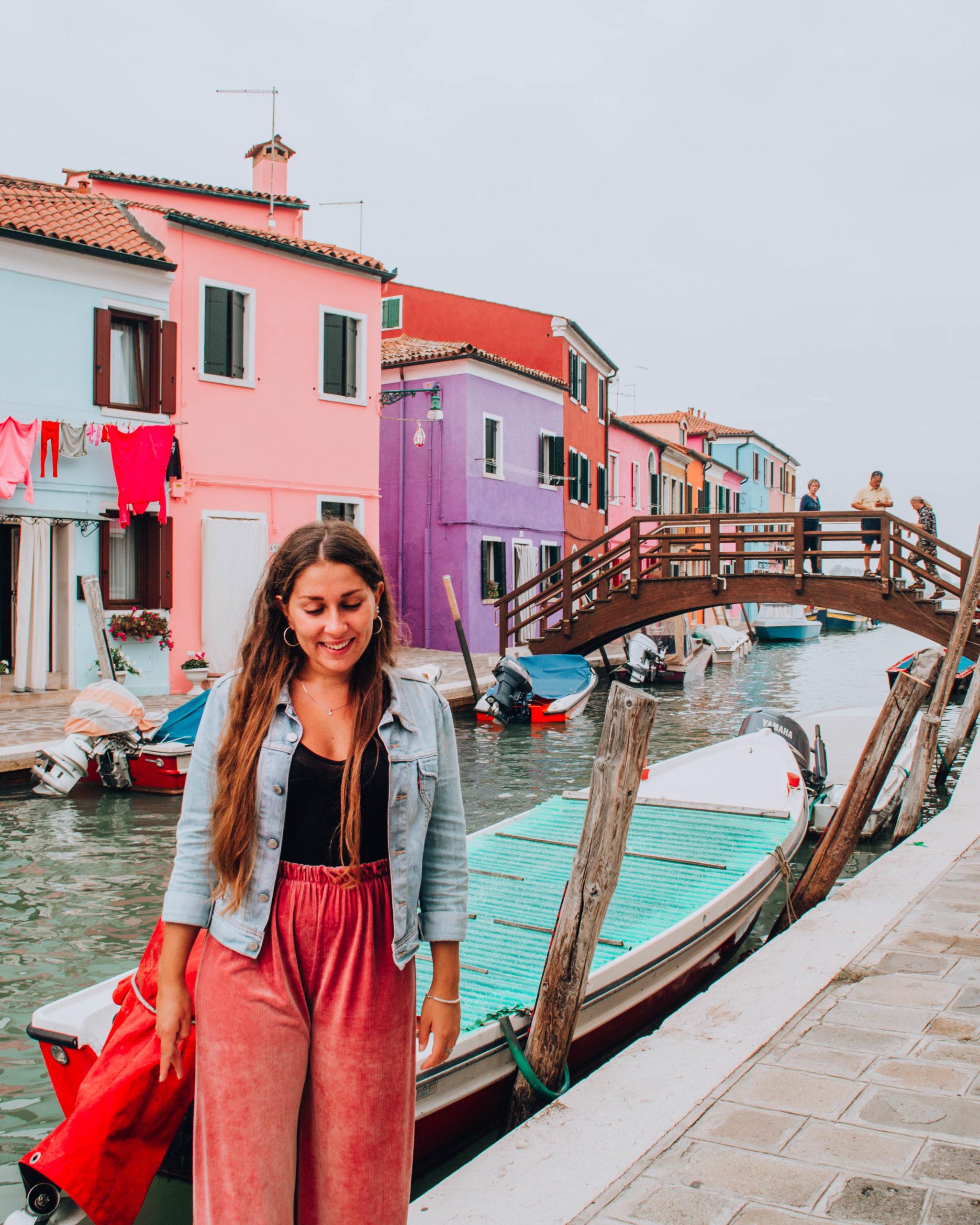 ragazza con pantalone rose davanti a piccolo ponte in legno e case colorate