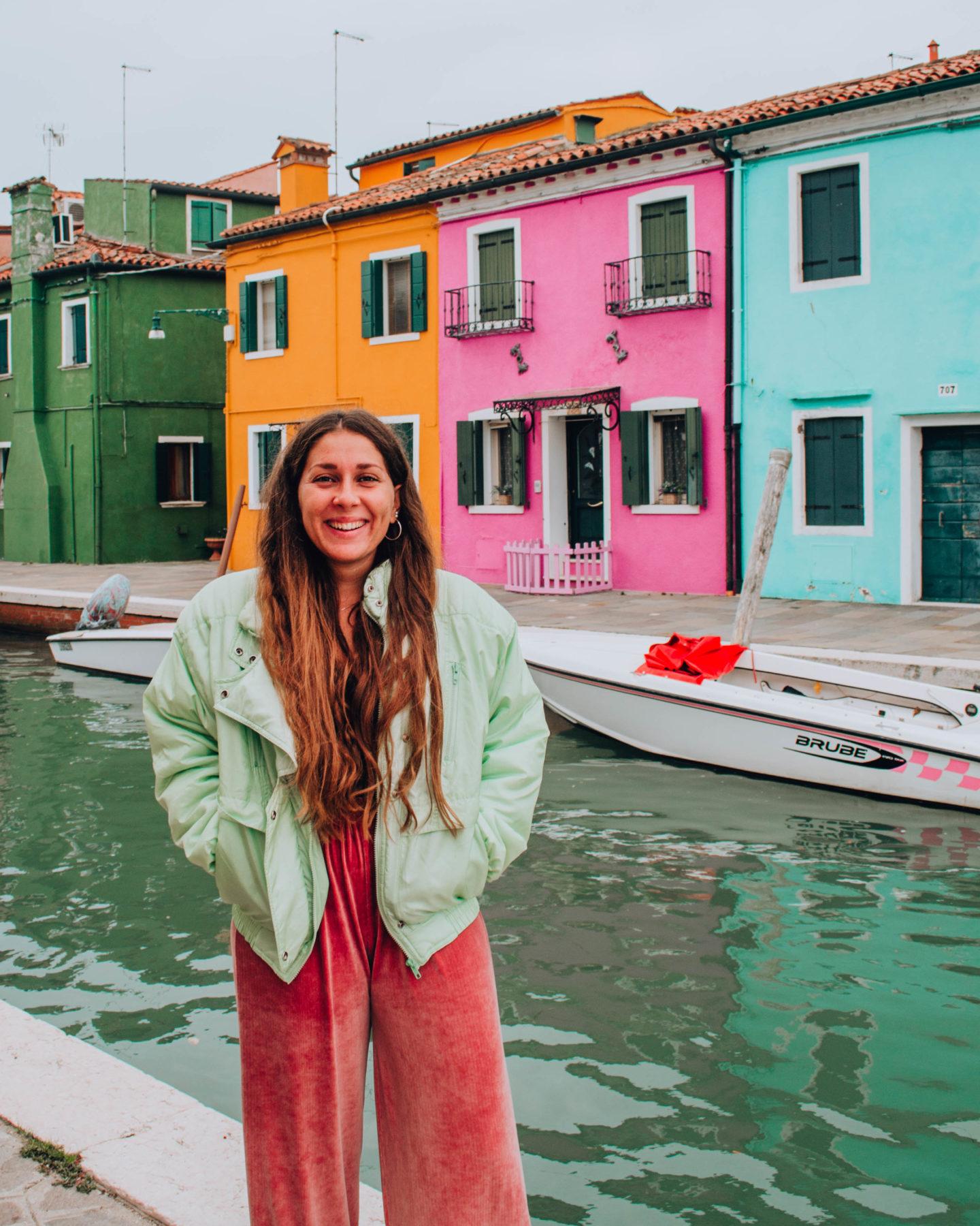 ragazza con pantalone rose e piumino verde davanti a case colorate e canale d'acqua