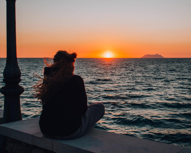 ragazza di spalle davanti al tramonto sul mare