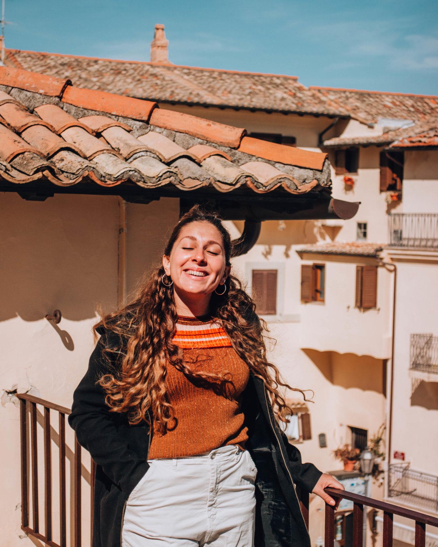 ragazza con maglia arancione e sole in faccia