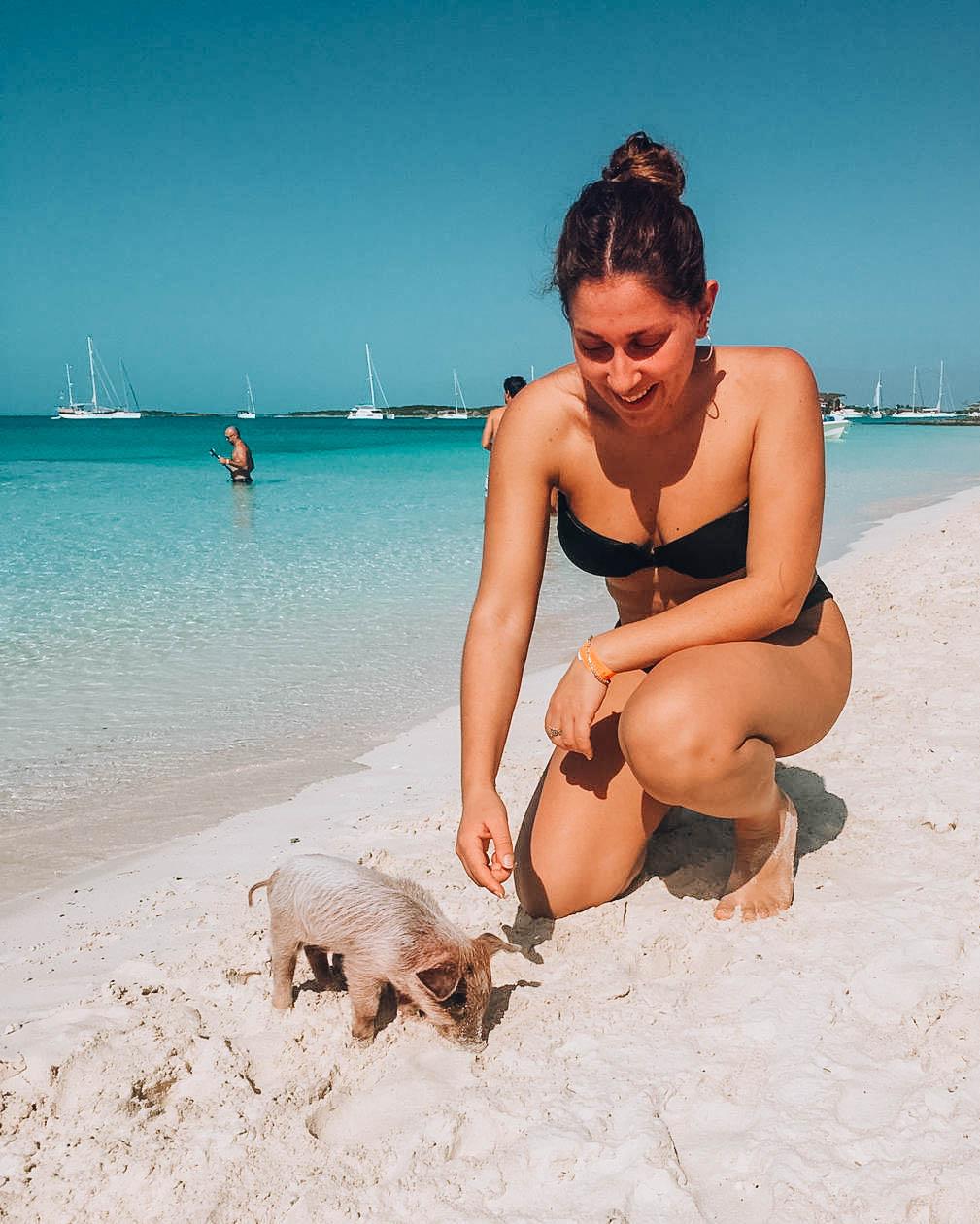 ragazza che accarezza maialino in spiaggia