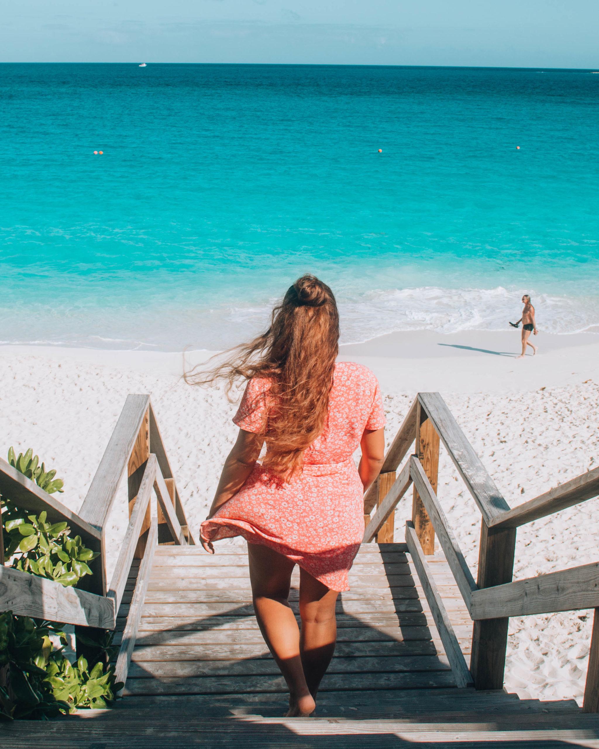 ragazza con vestito rosa che scende scale che portano a mare