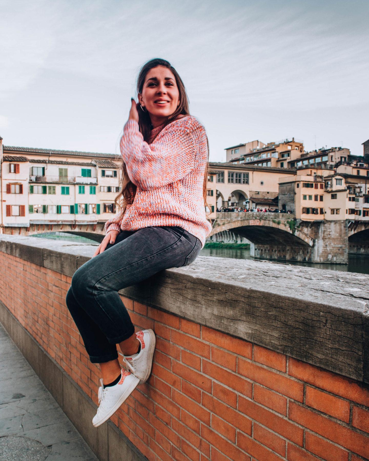 ragazza con maglione rosa seduta sul lungarno davanti ponte vecchio