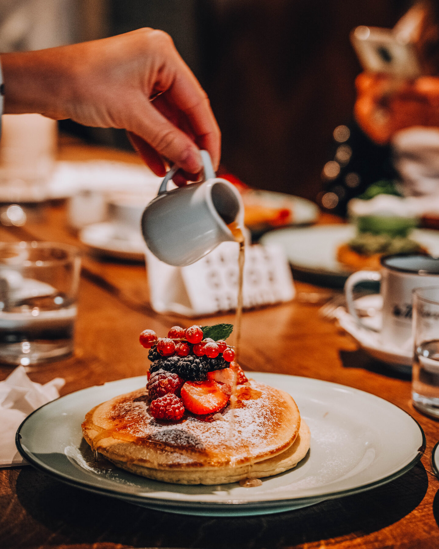 pancakes con frutti rossi e una mano che versa sciroppo d'acero