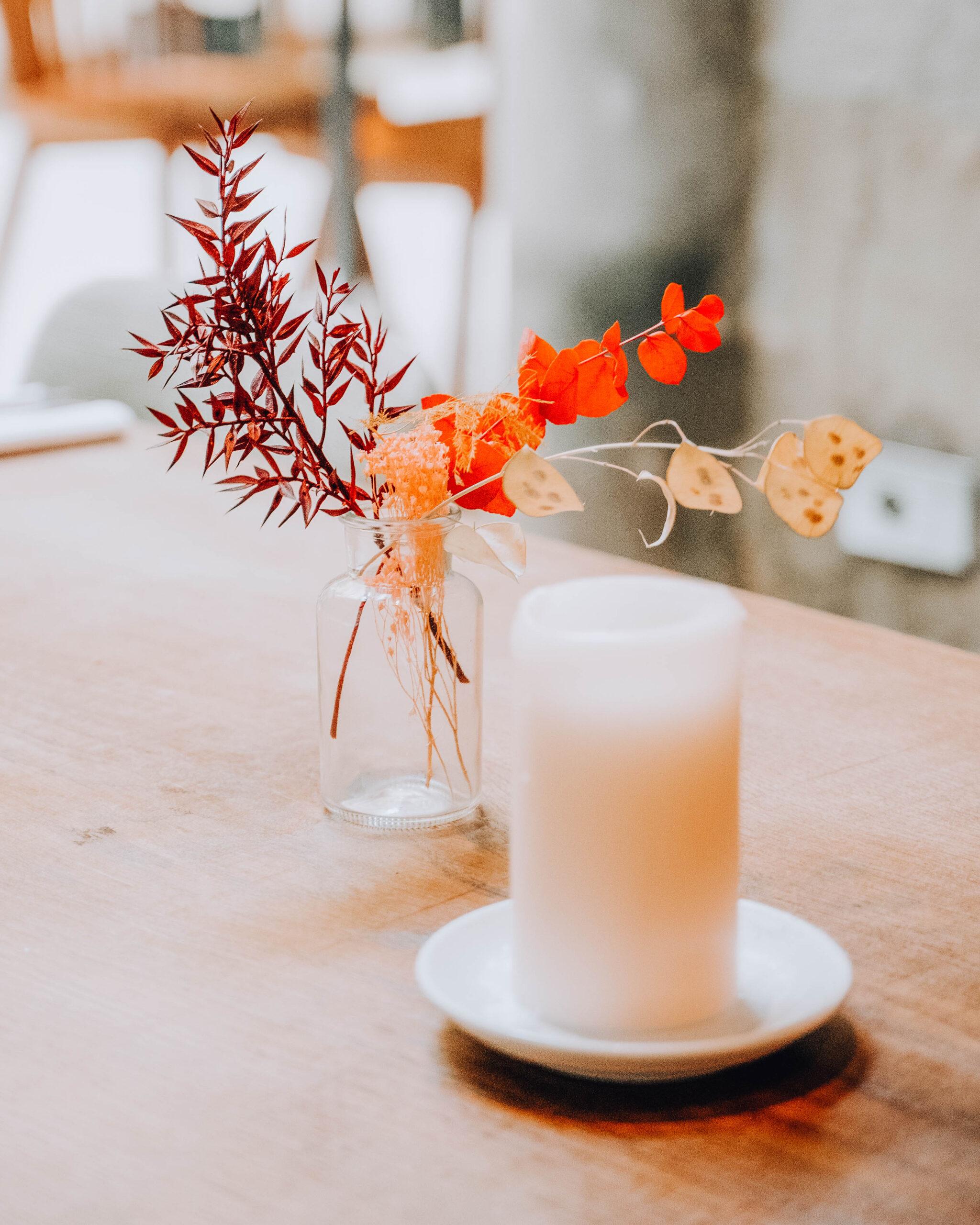 candela bianca e vasetto trasparente con fiori secchi