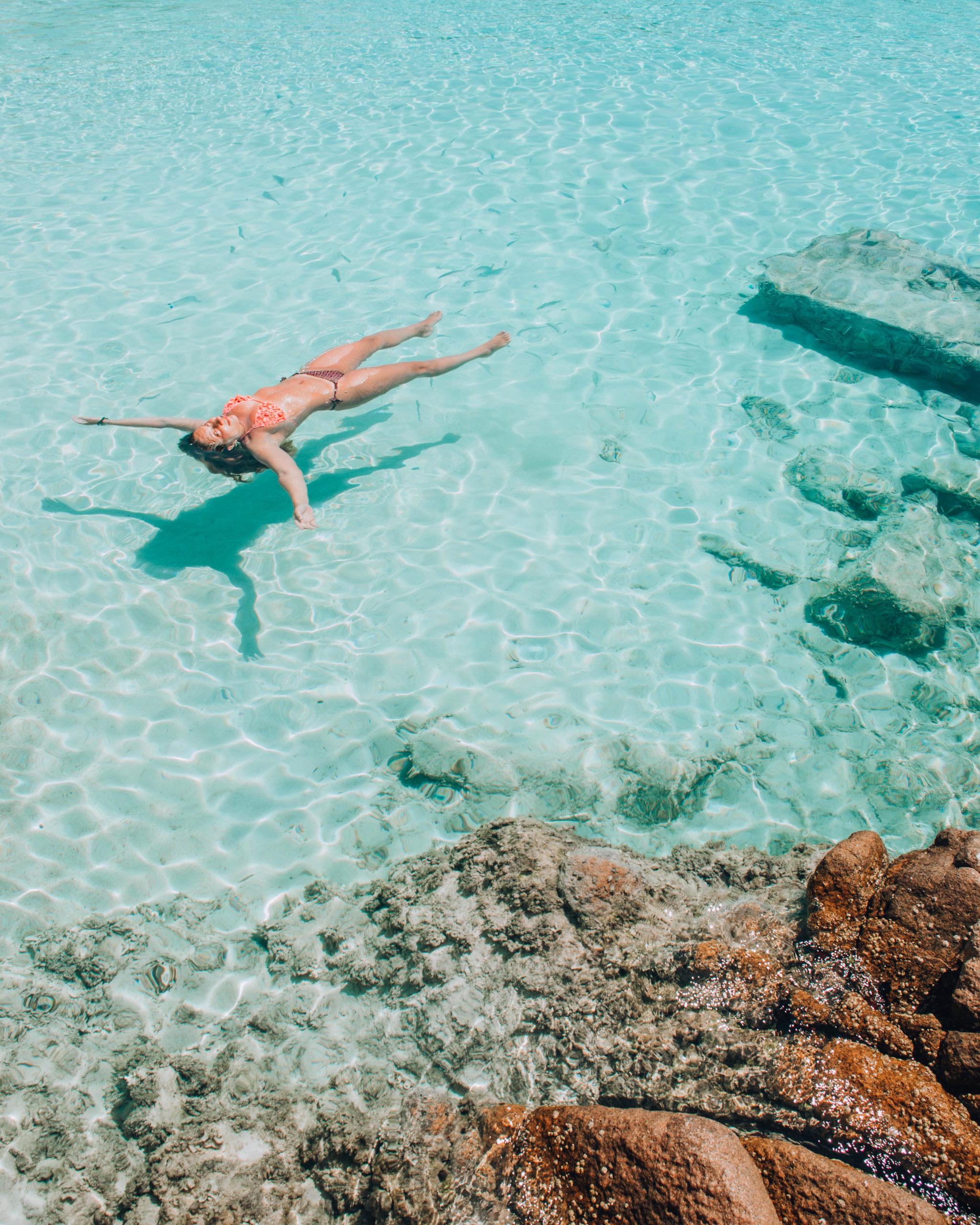 ragazza che galleggia in acqua turchese e trasparente
