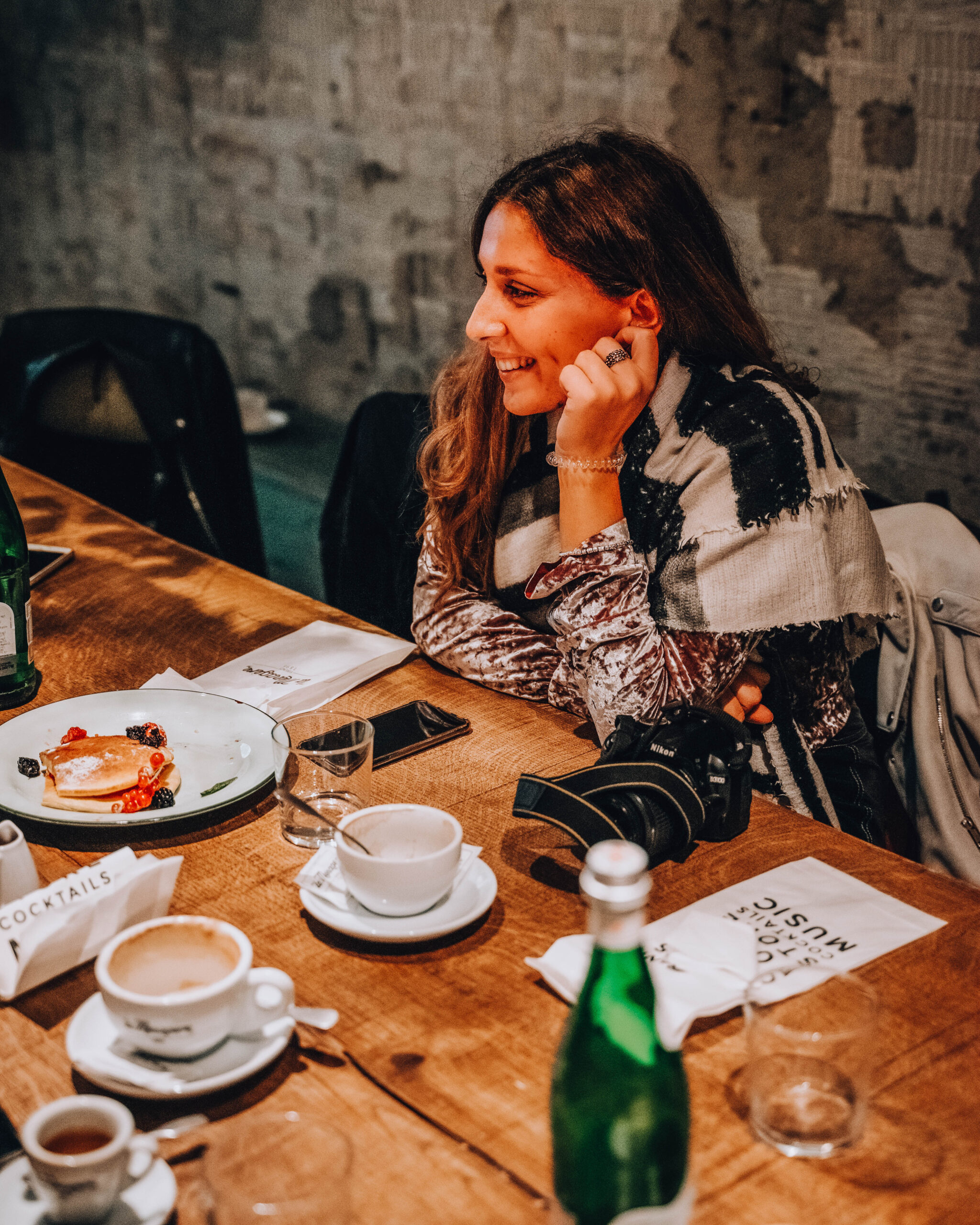 ragazza sorridente ad un tavolo in legno con piatto di pancakes