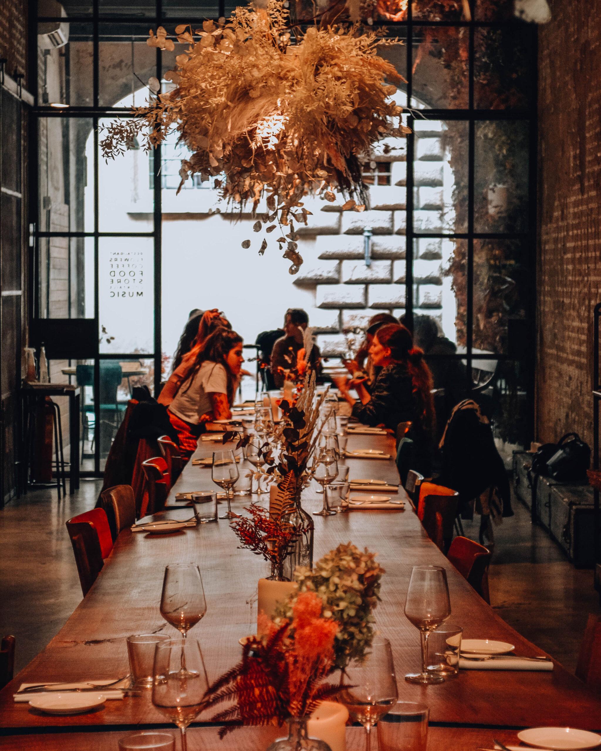 tavolo in legno con ragazze che mangiano in lontananza