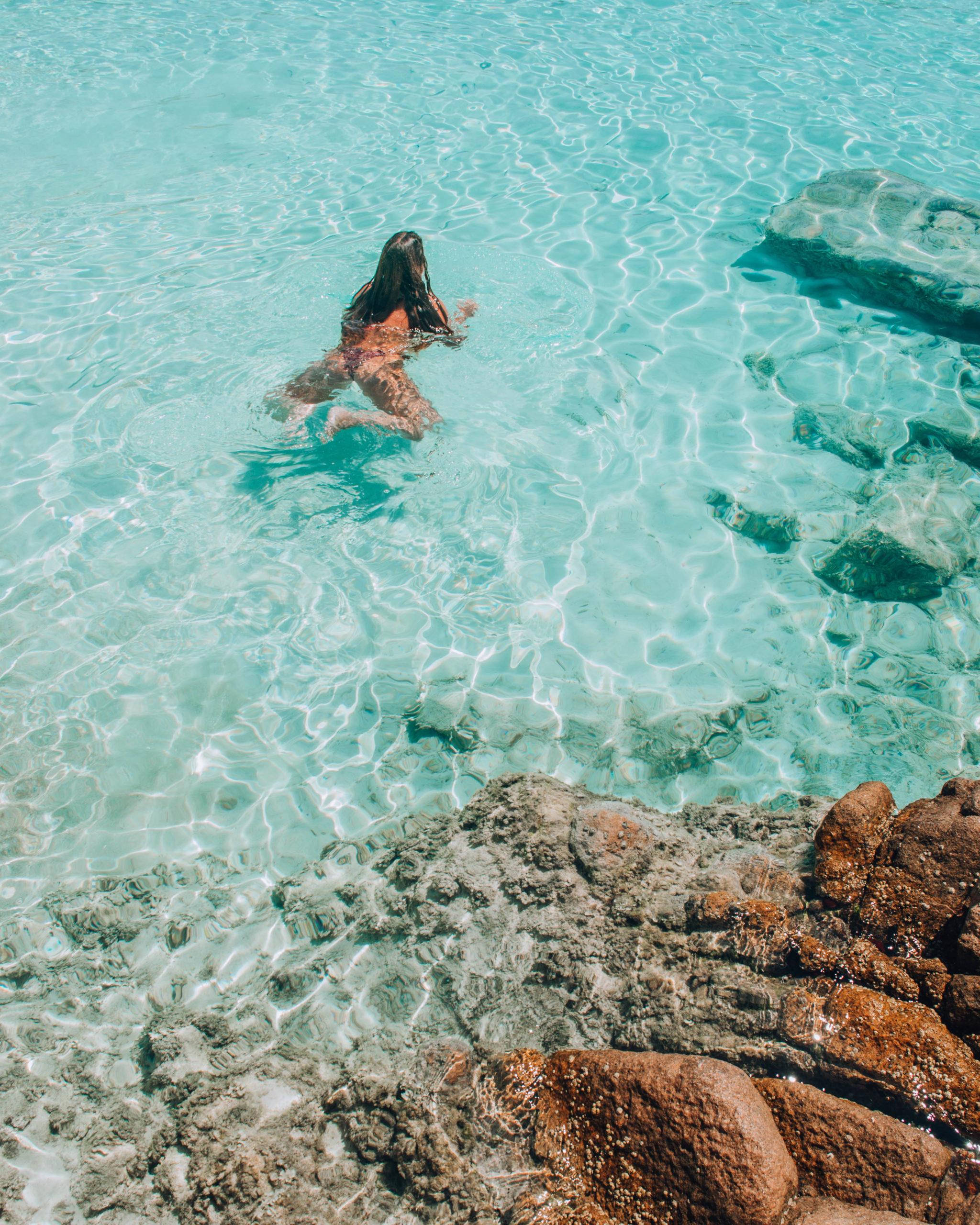 ragazza che nuota in acqua trasparente