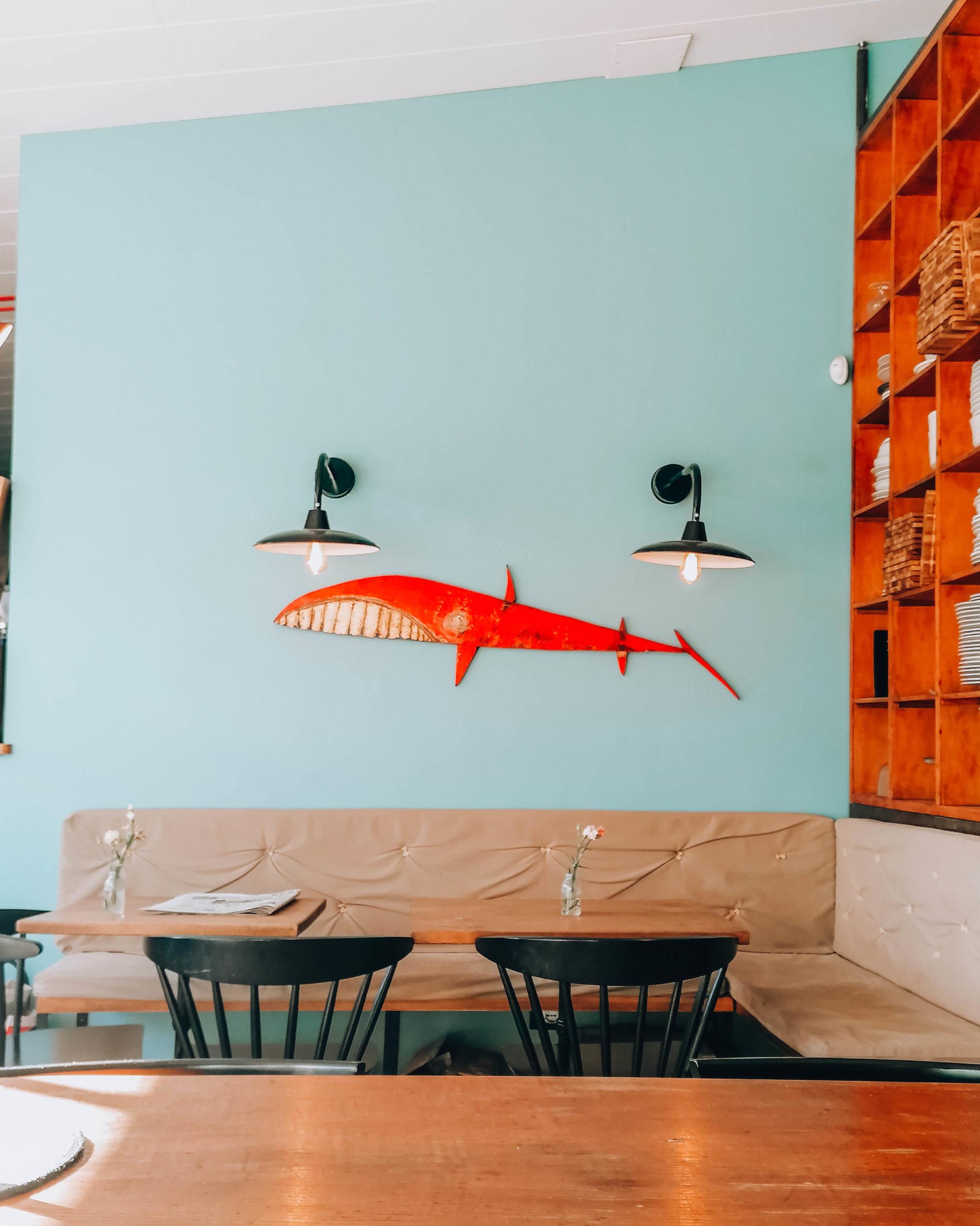 tavolo in legno con parete celeste con squalo disegnato