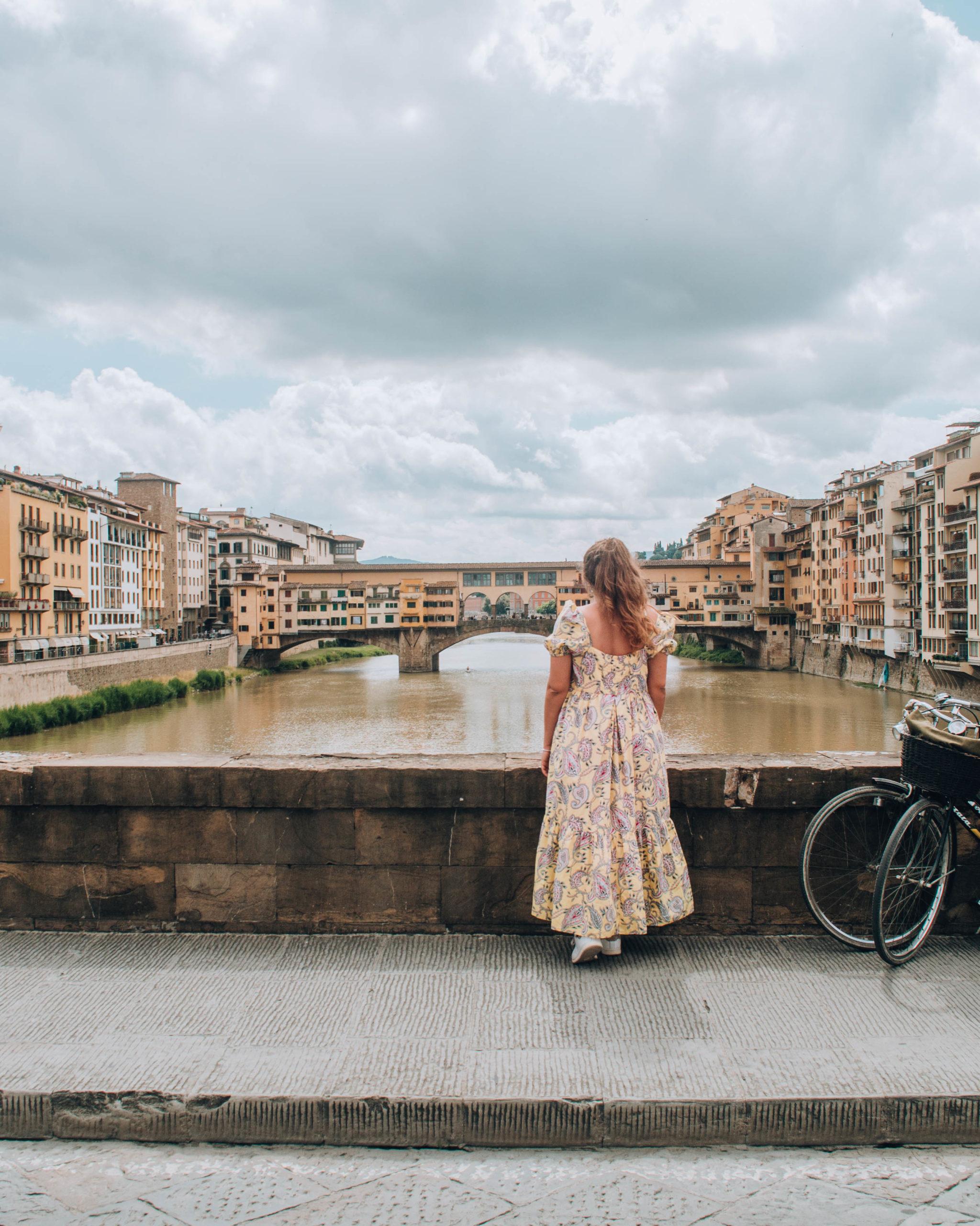 ragazza di spalle con vestito giallo davanti a ponte su fiume