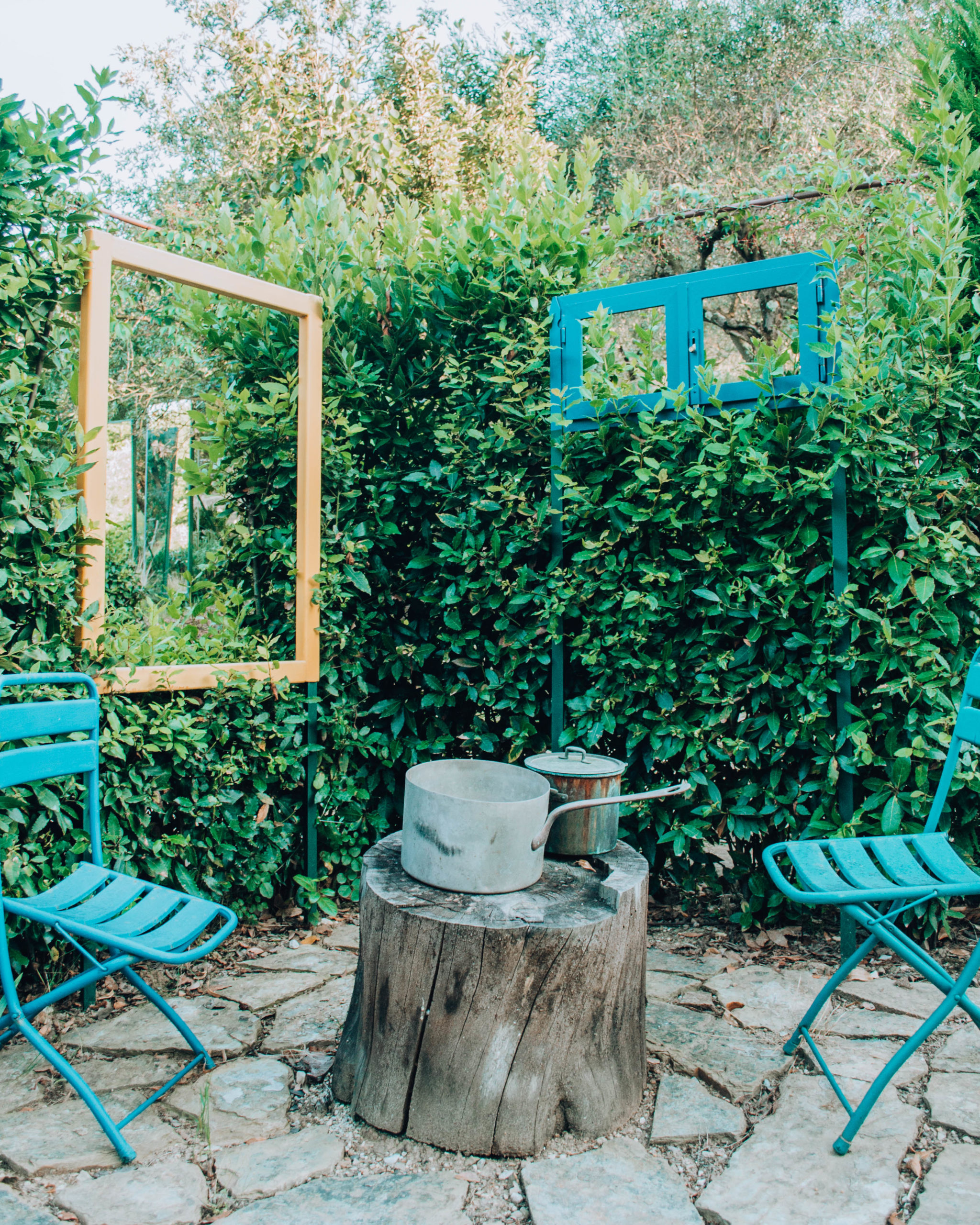 sedie e finestre in ferro colorato tra la siepe
