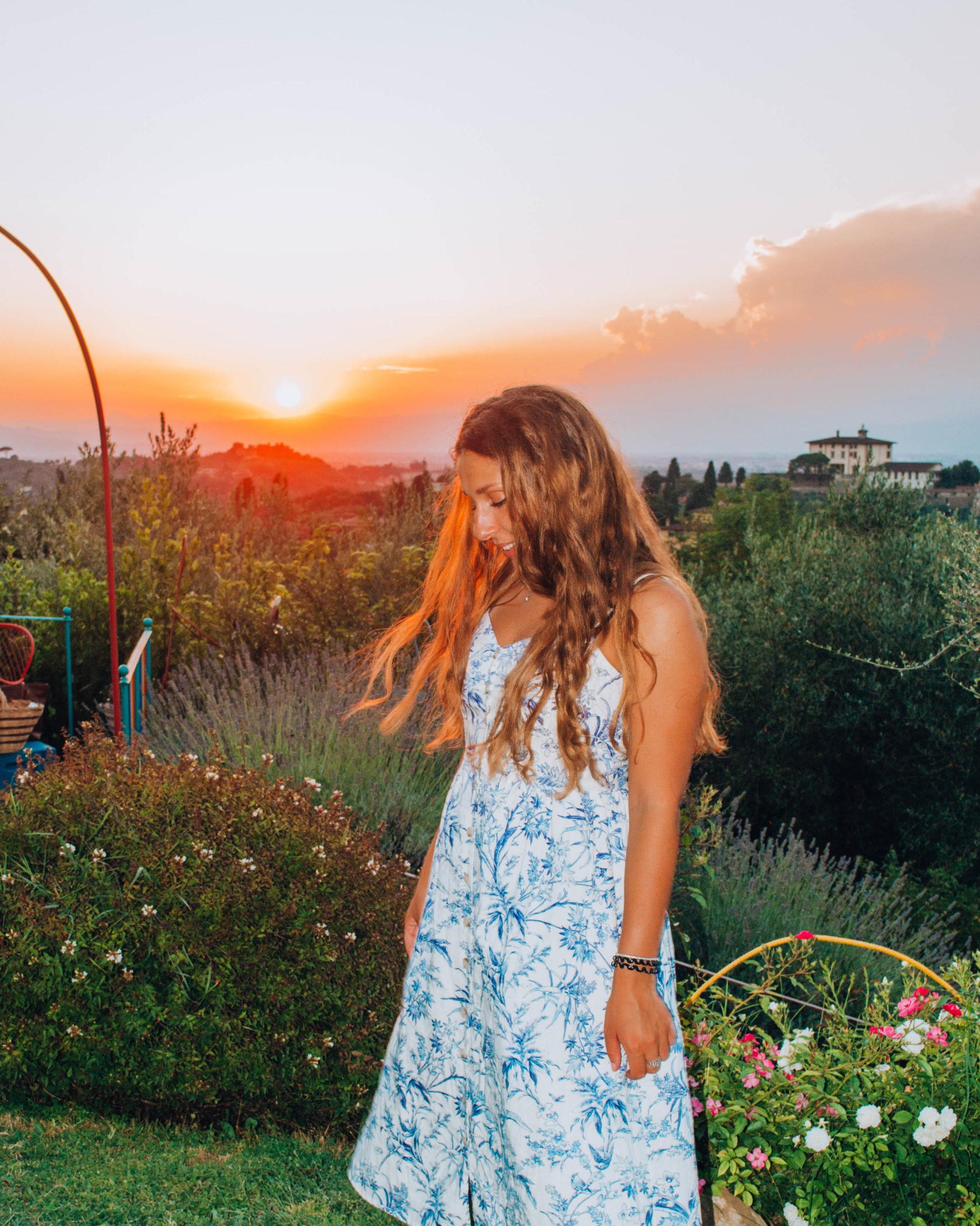 ragazza con vestito bianco distratta al tramonto