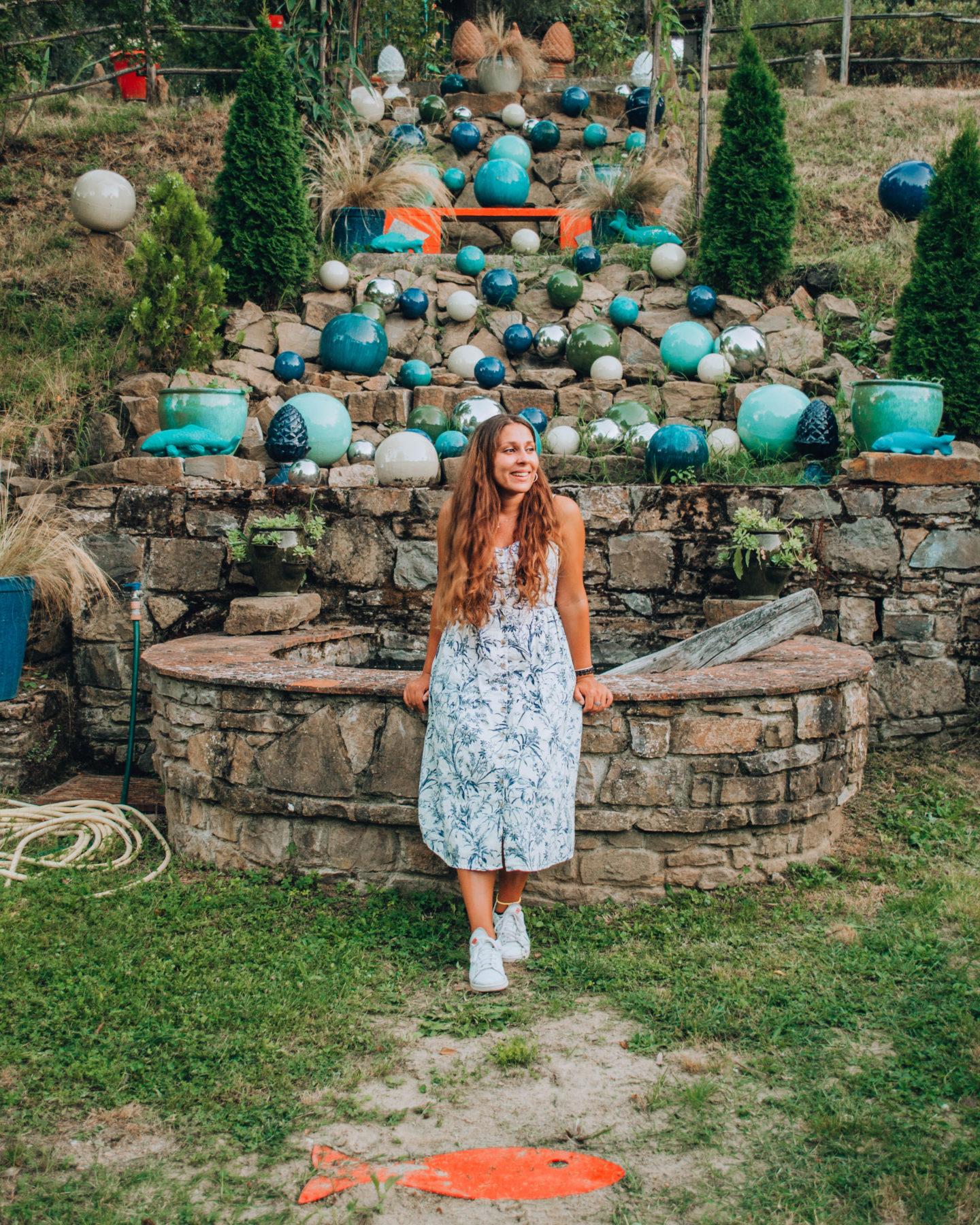 ragazza con vestito bianco davanti a una cascata di palle blu di ceramica