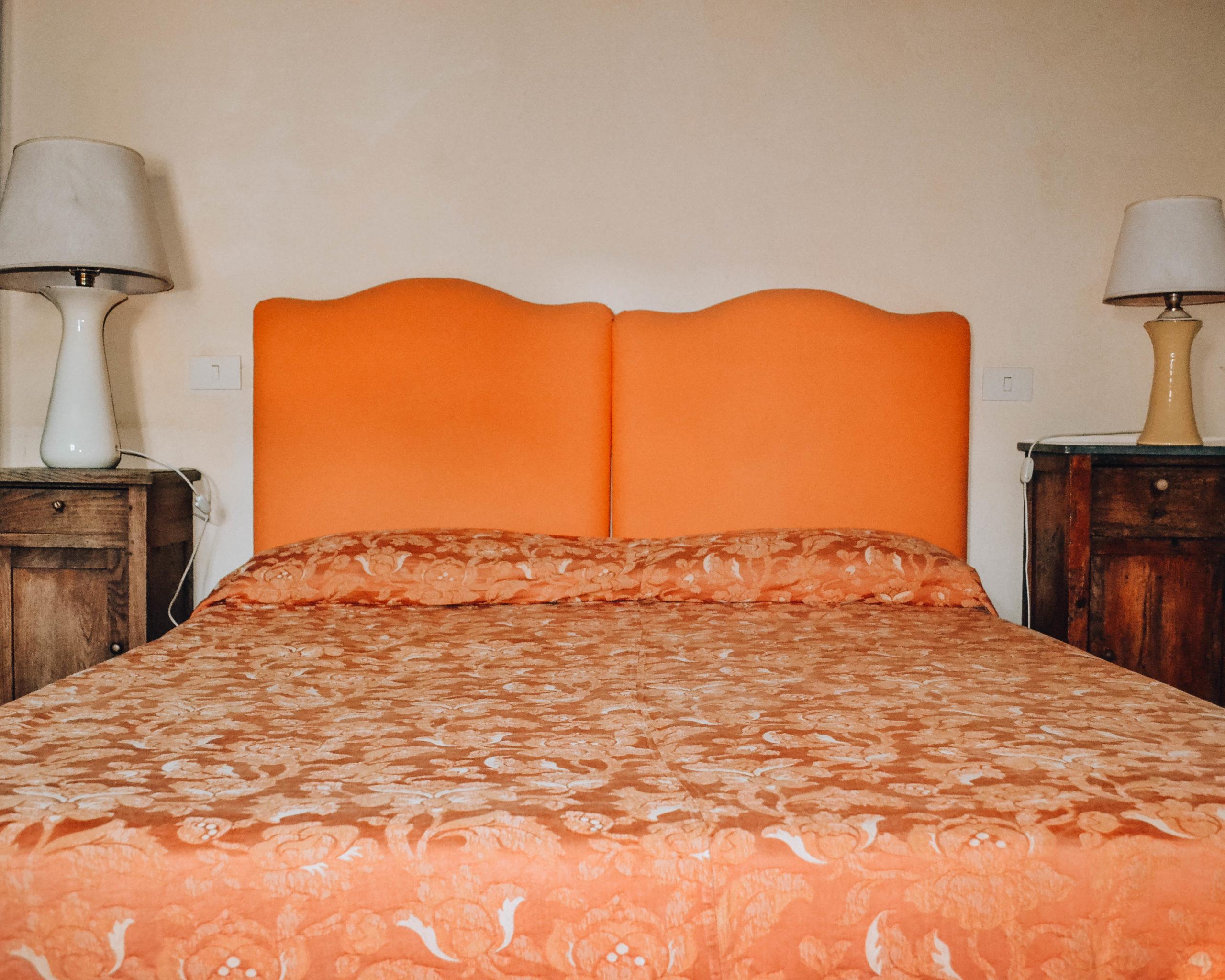 letto matrimoniale con coperta arancio e due comodini in legno