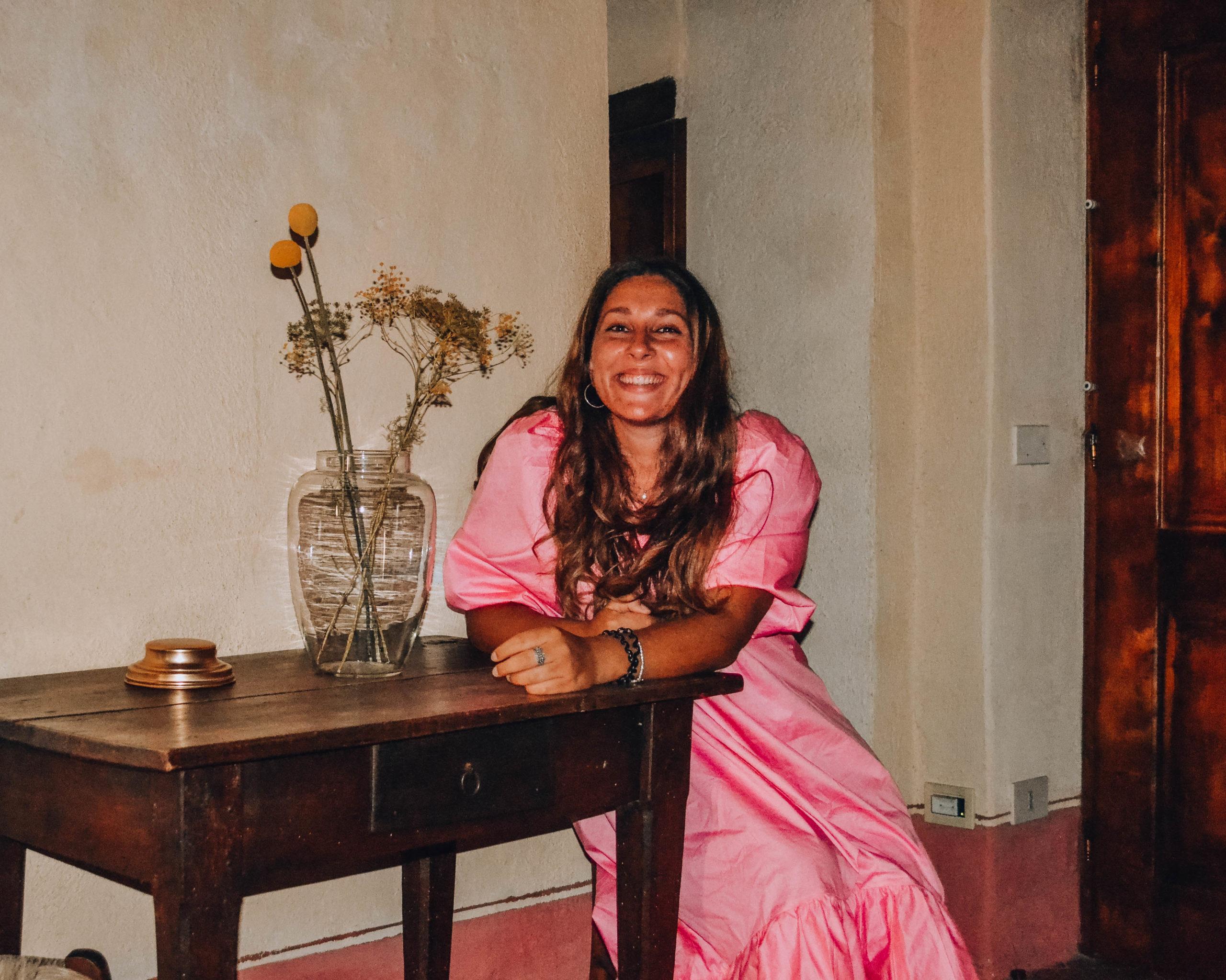 ragazza sorridente seduta a tavolo di legno con vaso trasparente