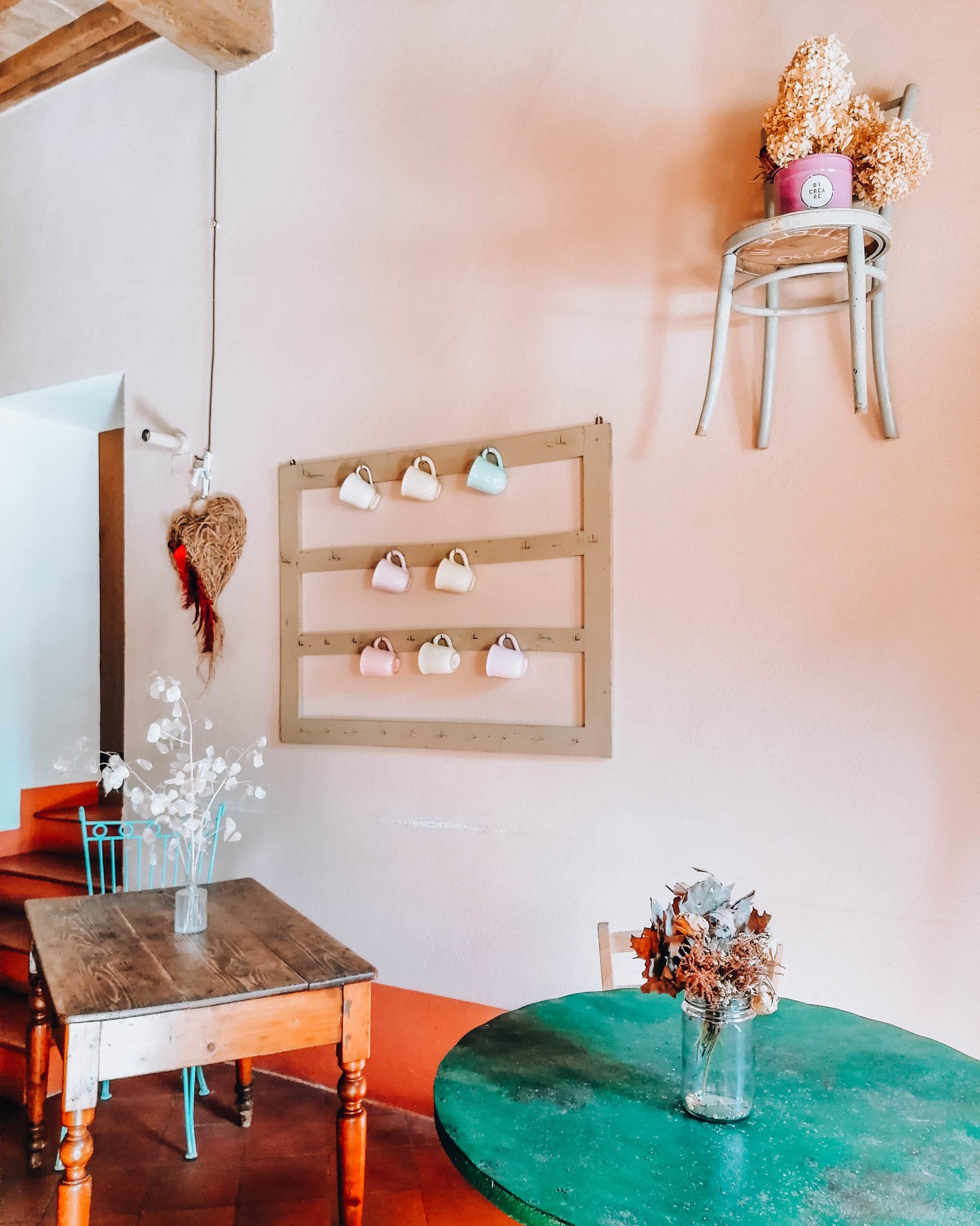 parete addobbata con sedia di paglia appena e tavoli in legno colorato