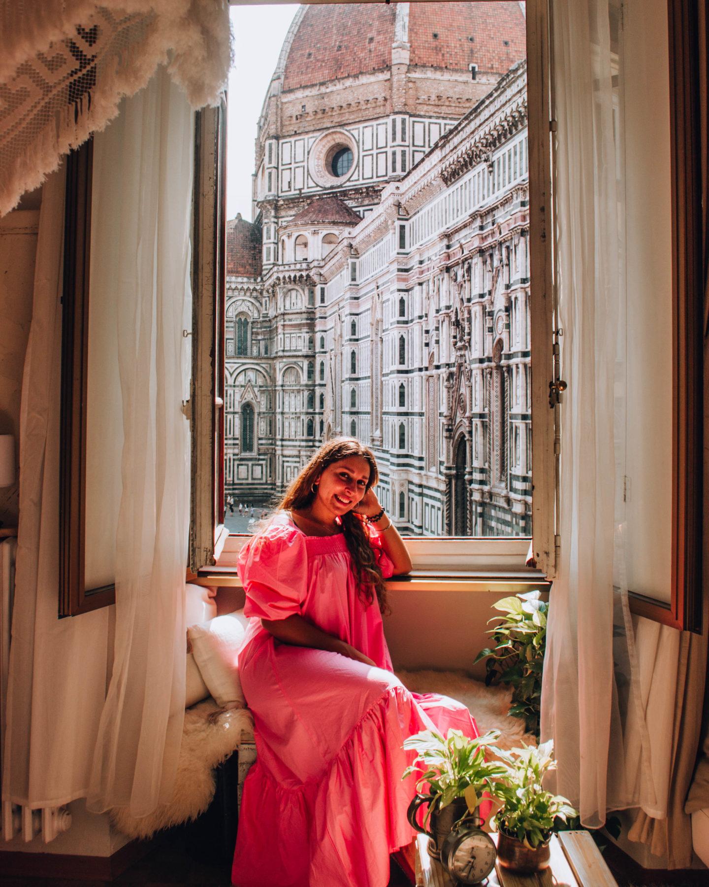 ragazza con vestito rosa alla finestra