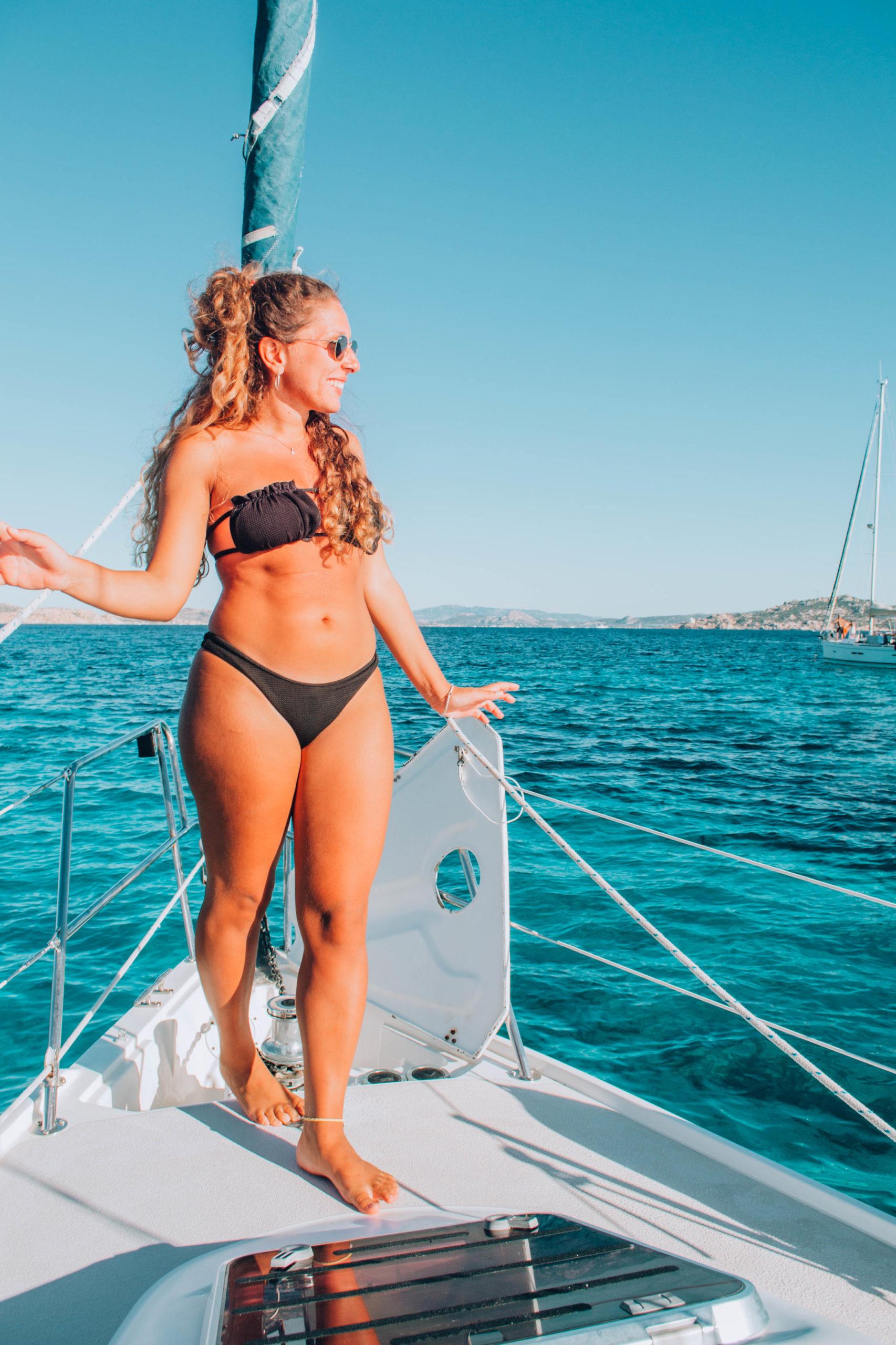 ragazza in bikini su prua di barca a vela