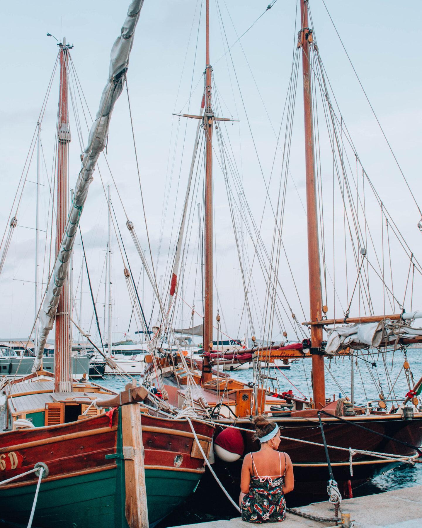 ragazza seduta di spalle davanti a barche a vela in legno