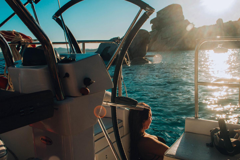 ragazza che guarda il tramonto su barca a vela