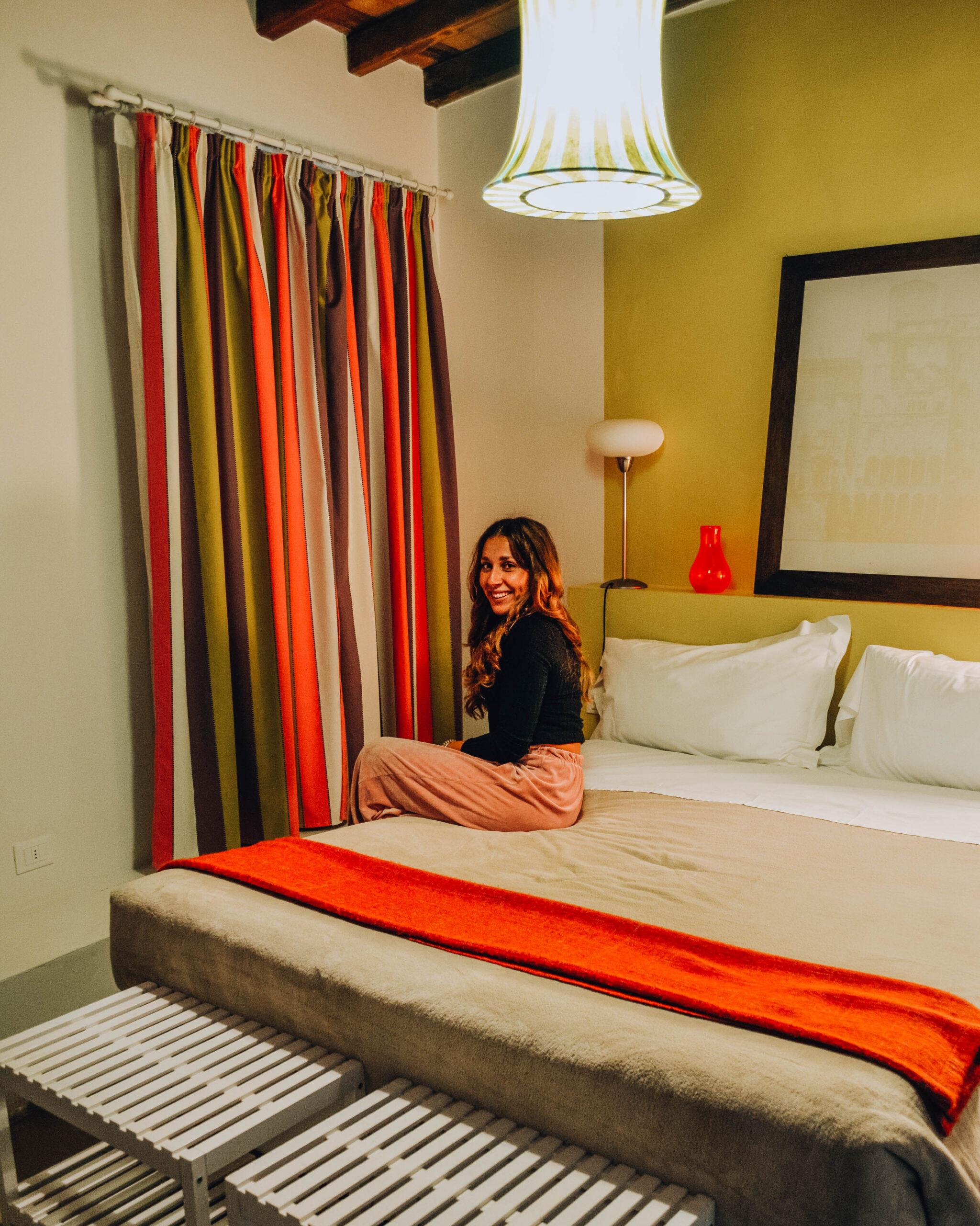 ragazza seduta di lato sul letto in stanza di b&b