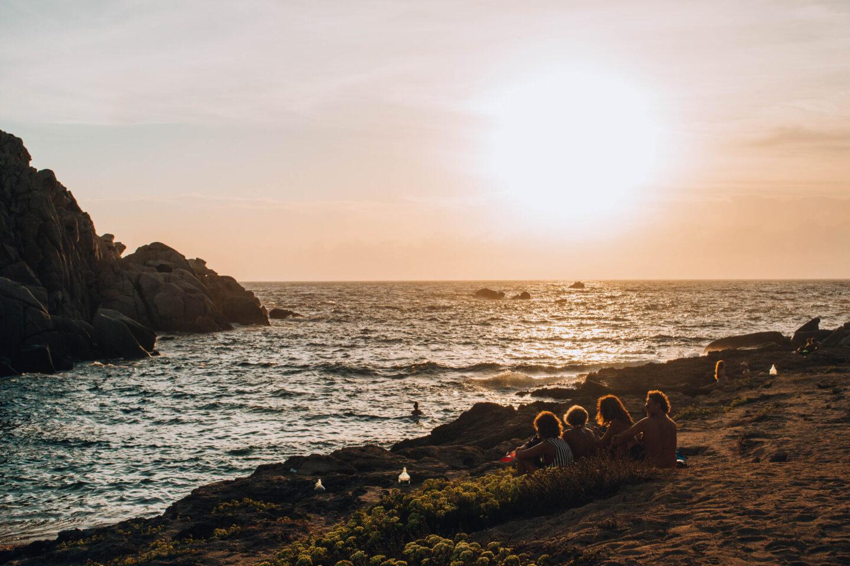 quattro persone di spalle che guardano il tramonto sul mare