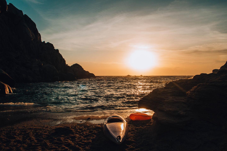 tramonto sul mare con canoa a riva