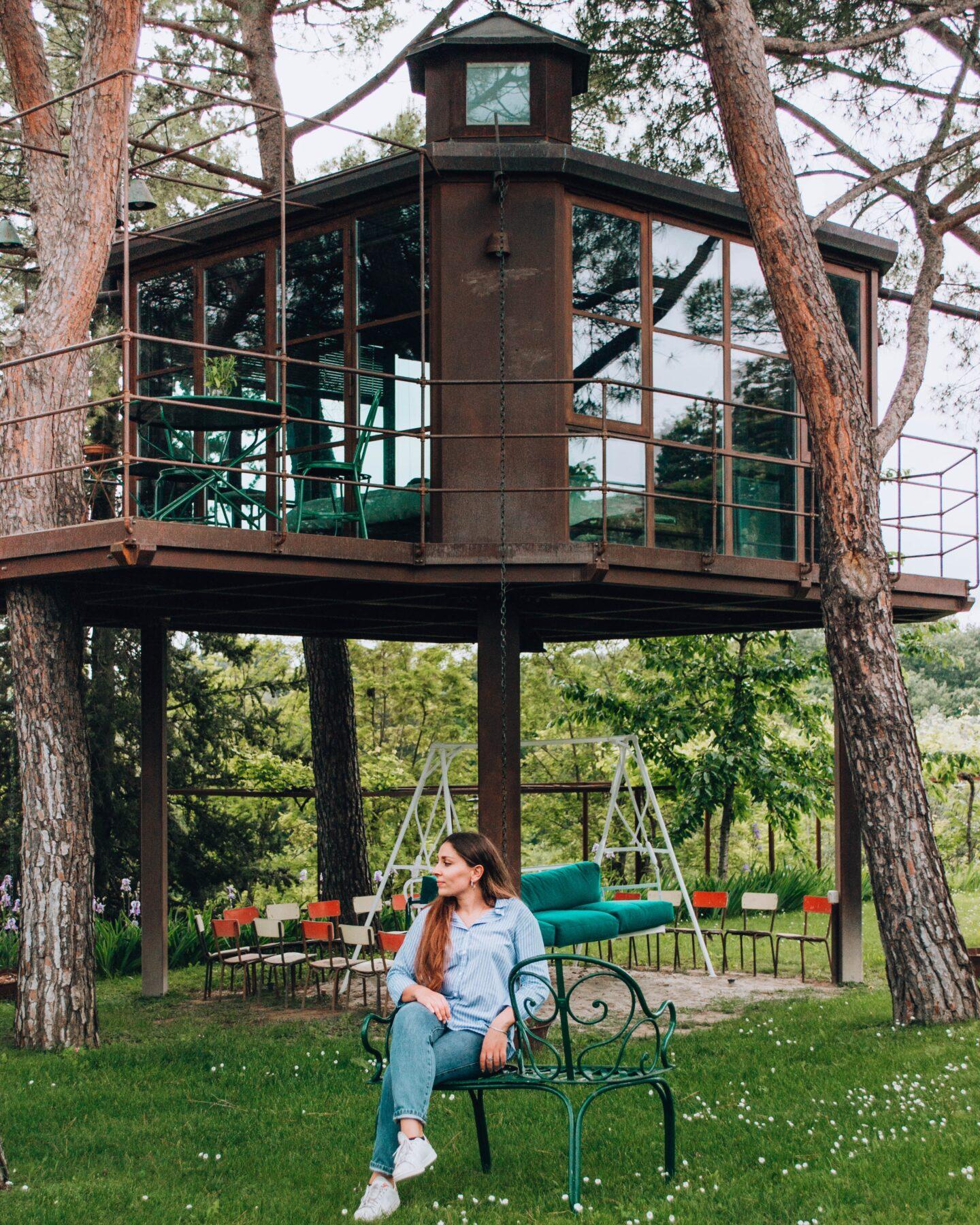ragazza seduta davanti a casa su albero