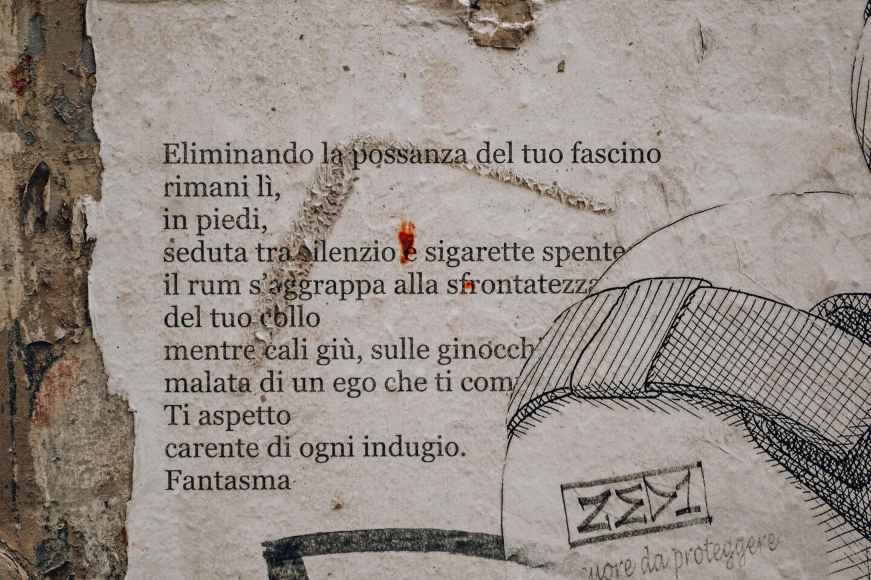 poesia scritta su foglio bianco affissa su muro in città