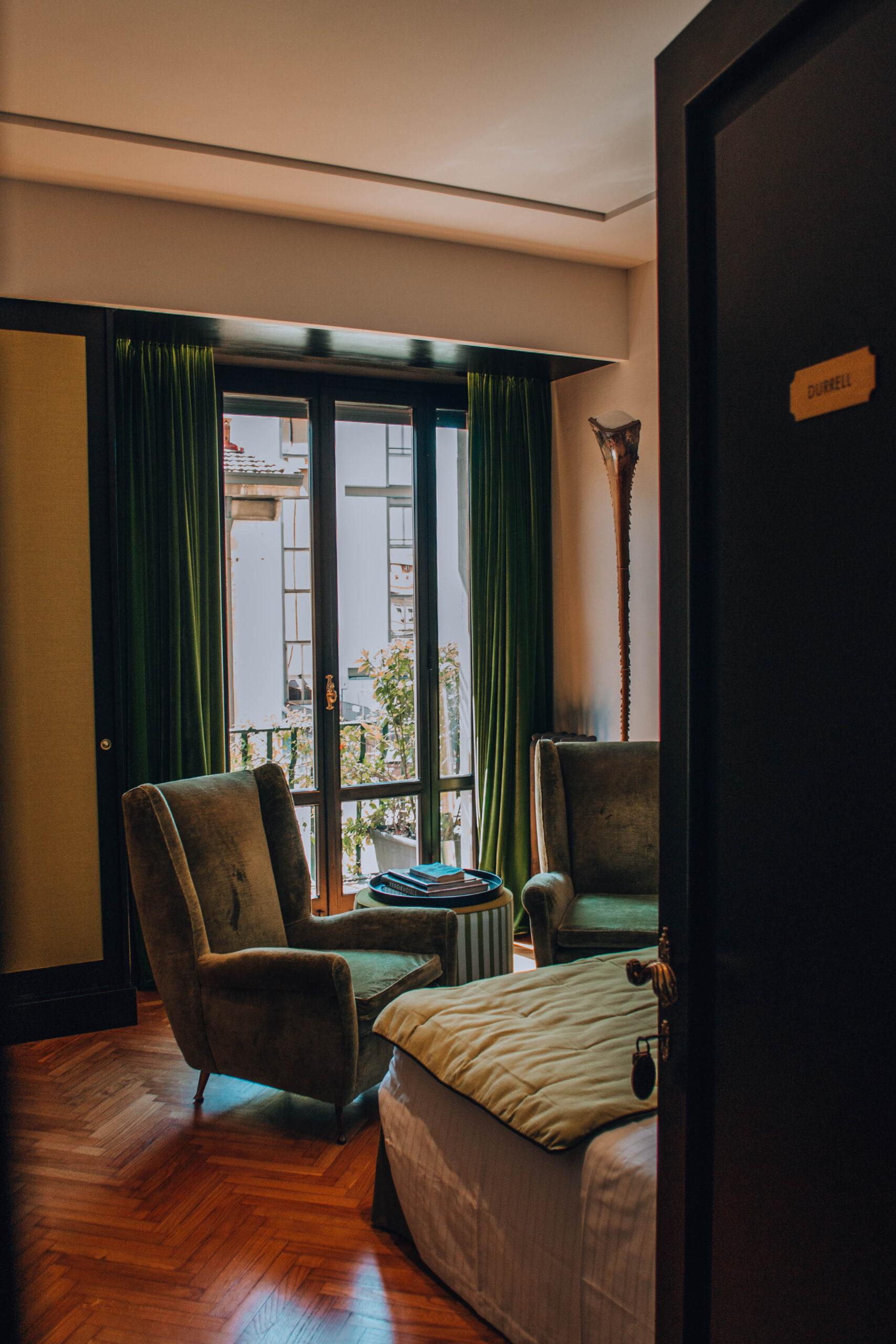 porta semi aperta di una stanza con poltrone verdi