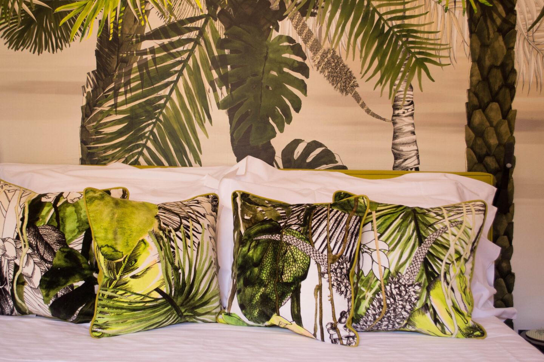 cuscini e testiera del letto arredati con foglie e palme