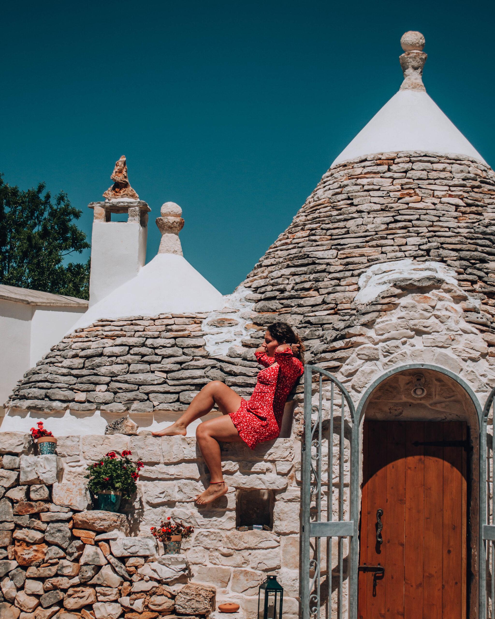 ragazza con vestito rosso sul tetto di un trullo