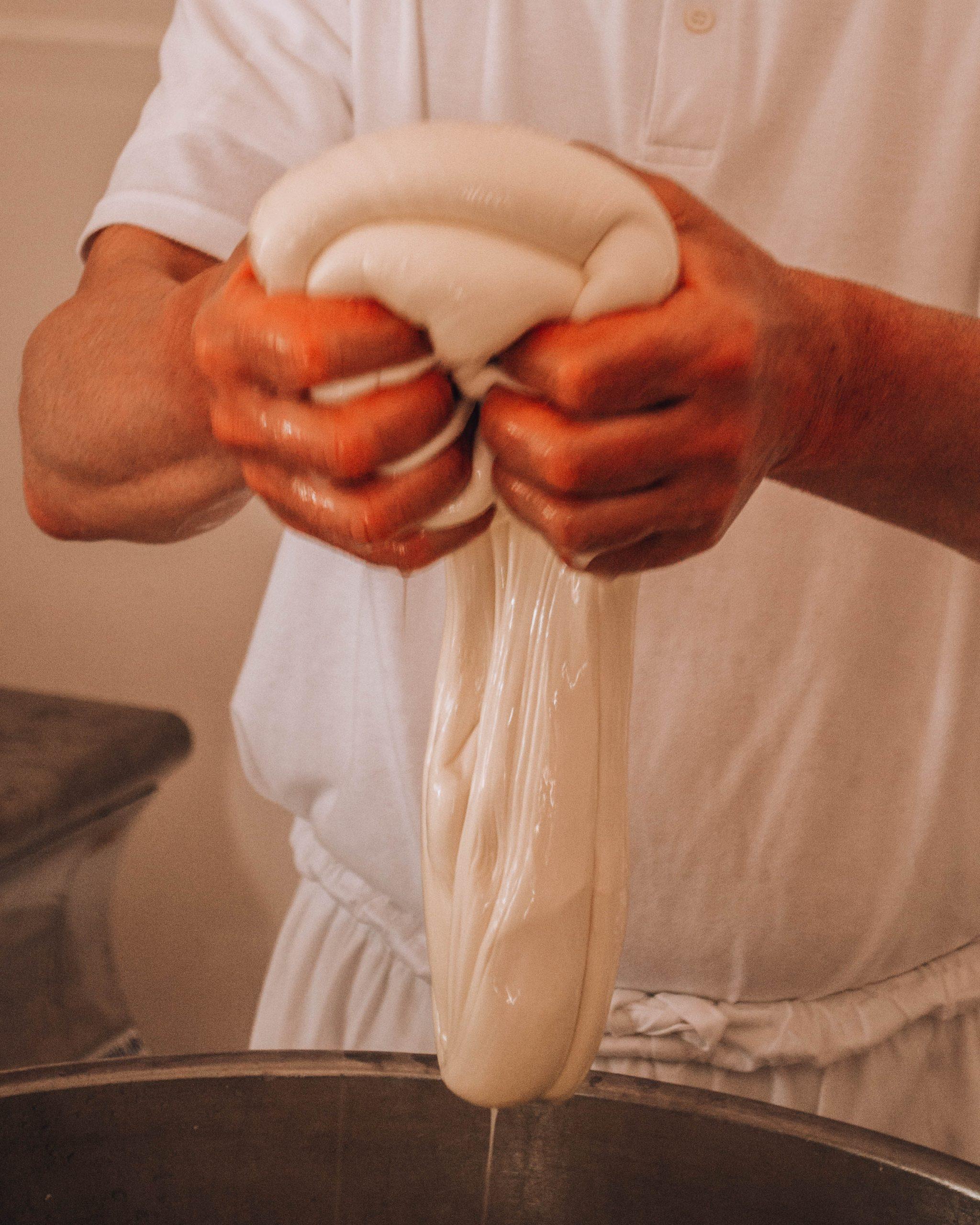 mani di pastore che fanno la mozzarella